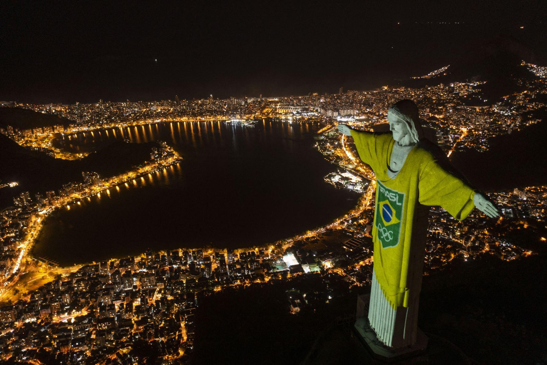 Vista aérea de la estatua del Cristo Redentor iluminada con los colores de la bandera brasileña y flechas olímpicas para marcar los 100 días hasta los Juegos Olímpicos de Tokio 2020 en Río de Janeiro, Brasil. Foto: AFP