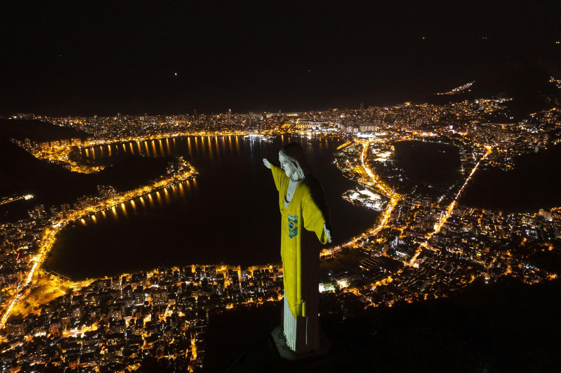 Vista aérea de la estatua del Cristo Redentor iluminada con los colores de la bandera brasileña para marcar los 100 días hasta los Juegos Olímpicos de Tokio 2020 en Río de Janeiro, Brasil. Foto: AFP
