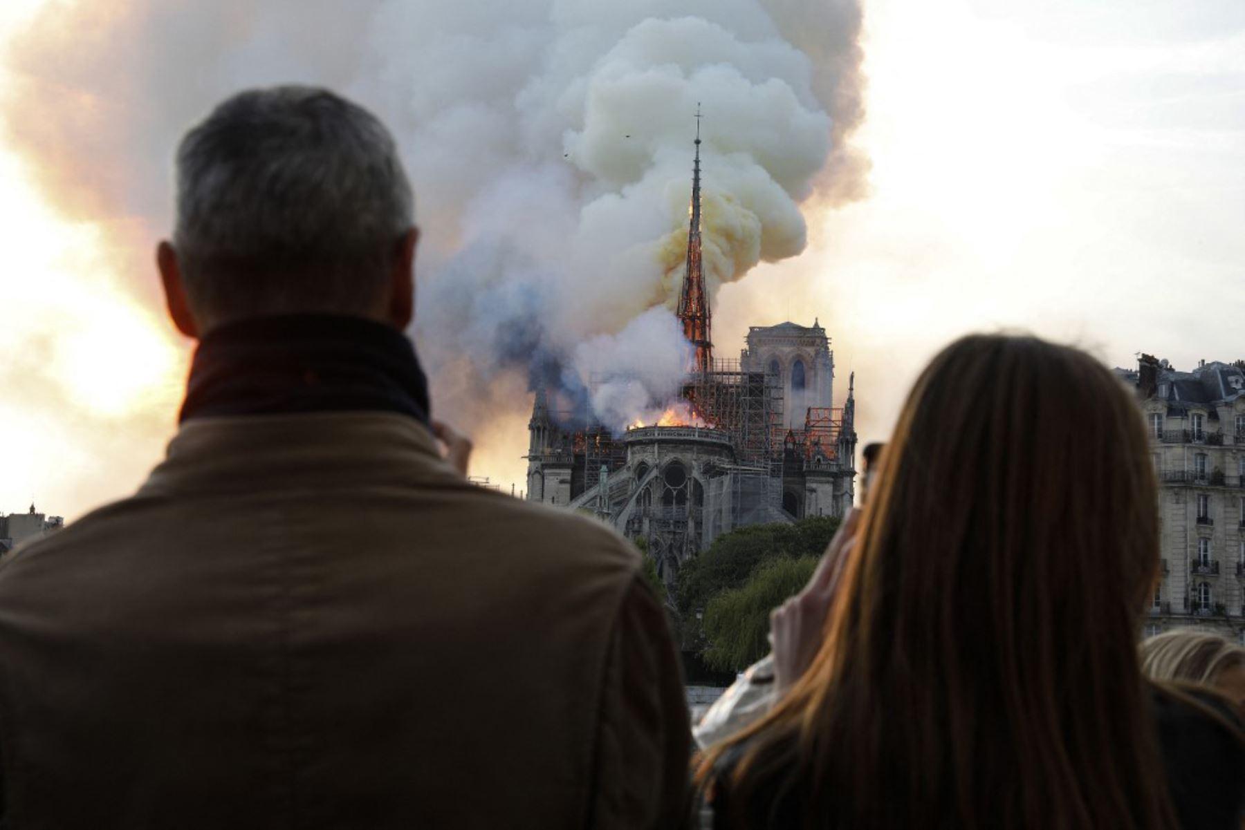 La gente reacciona al ver cómo las llamas envuelven el techo de la catedral de Notre-Dame de París en la capital francesa, París.  Foto: AFP