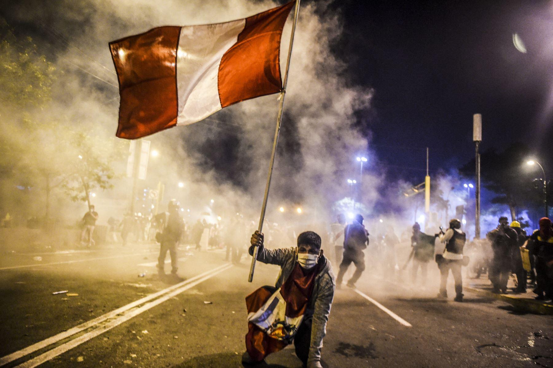 Noticias de actualidad, serie: el segundo lugar lo ocupa el fotógrafo peruano Ernesto Benavides. Un manifestante sostiene la bandera peruana durante las protestas que exige la renuncia de Manuel Merino a la presidencia, el 14 de noviembre del 2020, en Lima. Foto: Ernesto Benavides/AFP