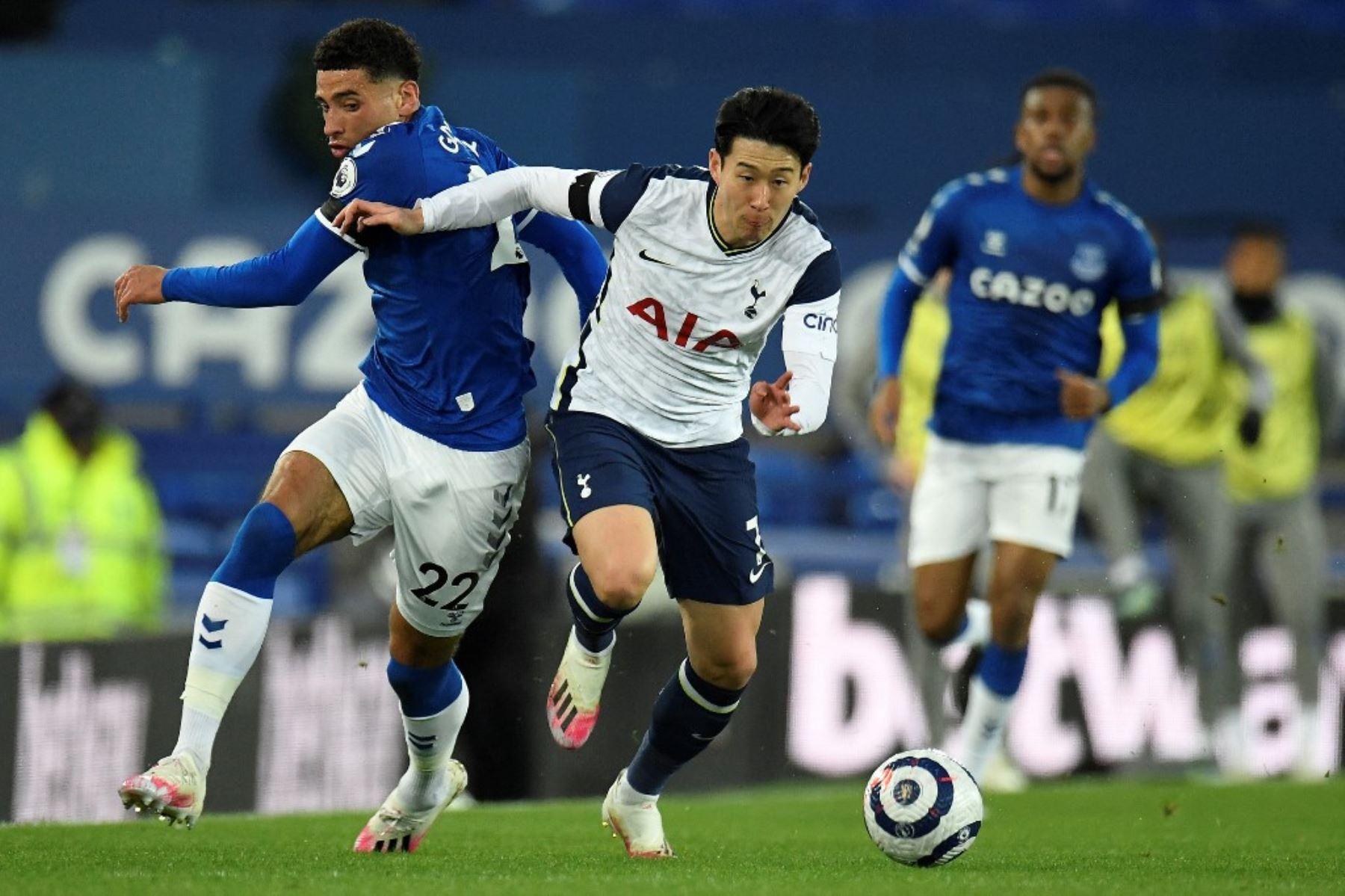 El centrocampista inglés del Everton Ben Godfrey (L) compite con el delantero surcoreano del Tottenham Hotspur Son Heung-Min (C) durante el partido de fútbol de la Premier League inglesa entre Everton y Tottenham Hotspur en Goodison Park en Liverpool. Foto: AFP