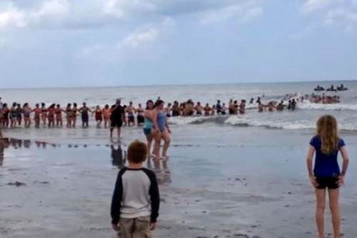 En el video se ve una larga cadena humana formada desde la orilla de la playa que penetra en un mar picado con unos bañistas a la cabeza llevando un flotador. Foto: Captura de Internet