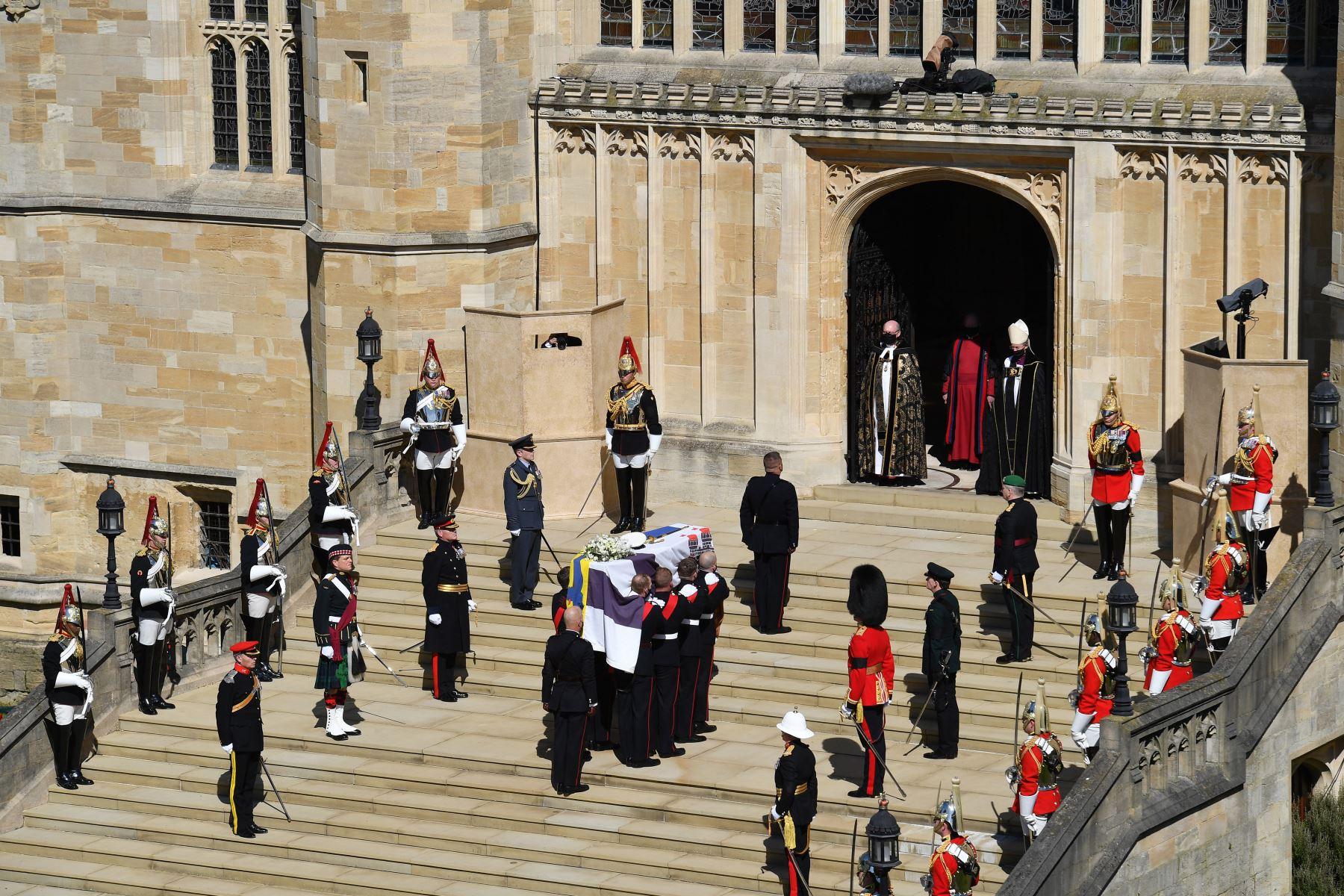 Los portadores del féretro de los Royal Marines que llevan el ataúd y los miembros de las fuerzas armadas hacen una pausa de un minuto de silencio en los escalones occidentales de la Capilla de San Jorge para marcar el inicio del funeral del príncipe Felipe de Gran Bretaña, duque de Edimburgo. Foto: AFP