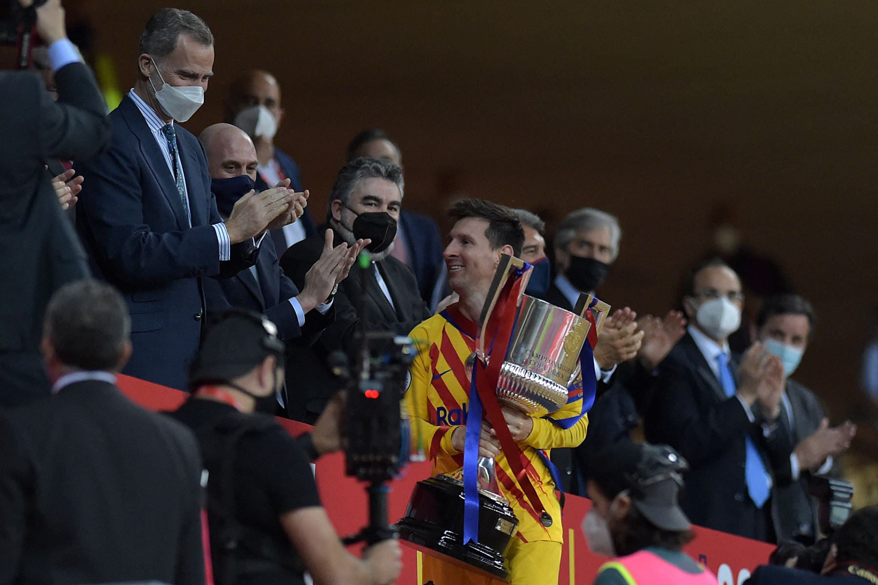 El delantero argentino del Barcelona Lionel Messi sostiene el trofeo después de recibirlo de manos del rey Felipe VI (izq.) De España al final de la final de la Copa del Rey de España entre el Athletic Club de Bilbao y el FC Barcelona en el estadio de La Cartuja de Sevilla. Foto: AFP