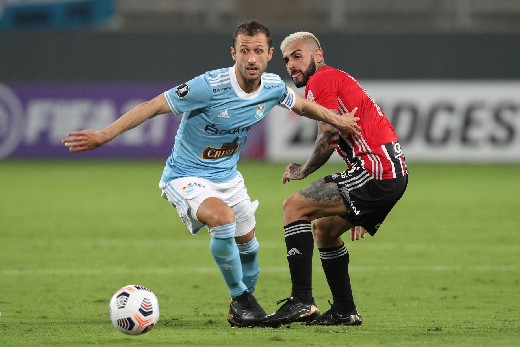 El jugador de Sporting Cristal, Horacio Calcaterra y el jugador Liziero de  Sao Paulo compiten por el balón durante el partido de la fase de grupos de la Copa Libertadores en el Estadio Nacional. Foto: AFP