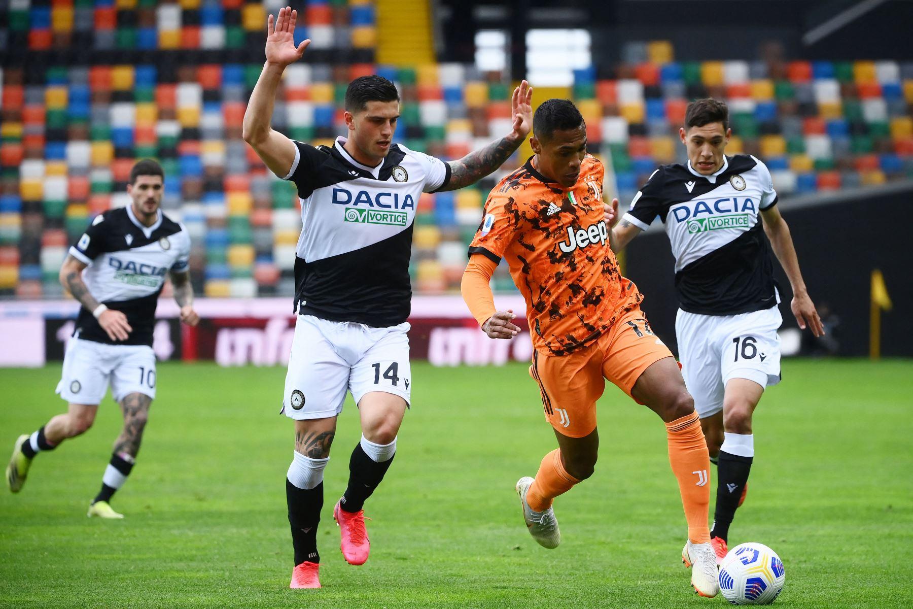 El defensor italiano del Udinese Kevin Bonifazi  lucha por el balón con el defensor brasileño de la Juventus Alex Sandro durante el partido de fútbol de la Serie A italiana entre el Udinese y la Juventus. Foto: AFP