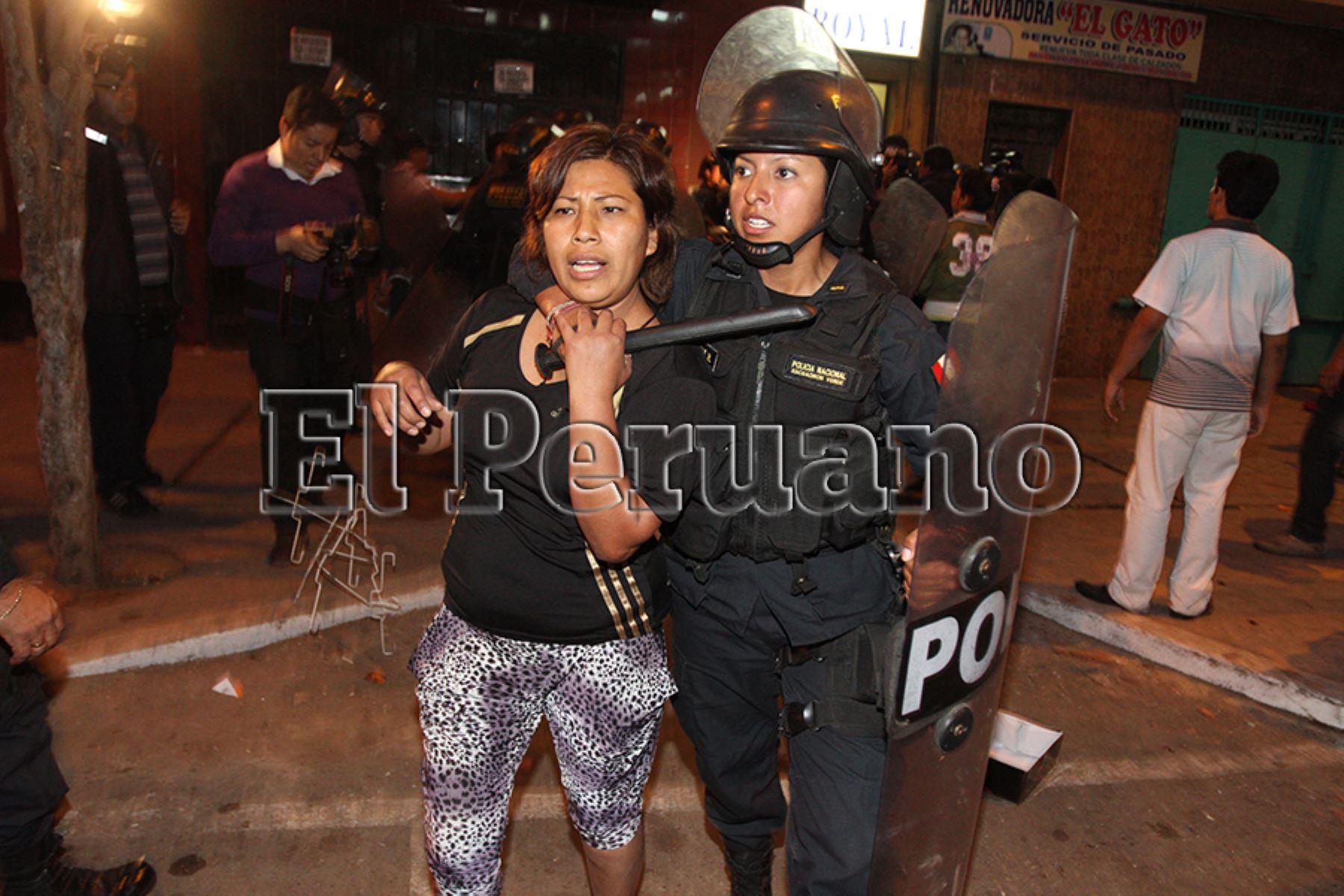 Lima – 25 octubre 2012 / Mujer policía, detiene a una de las personas, que ocasionaron violentos disturbios en el desalojo de ambulantes en Gamarra.  Foto: Archivo EL PERUANO