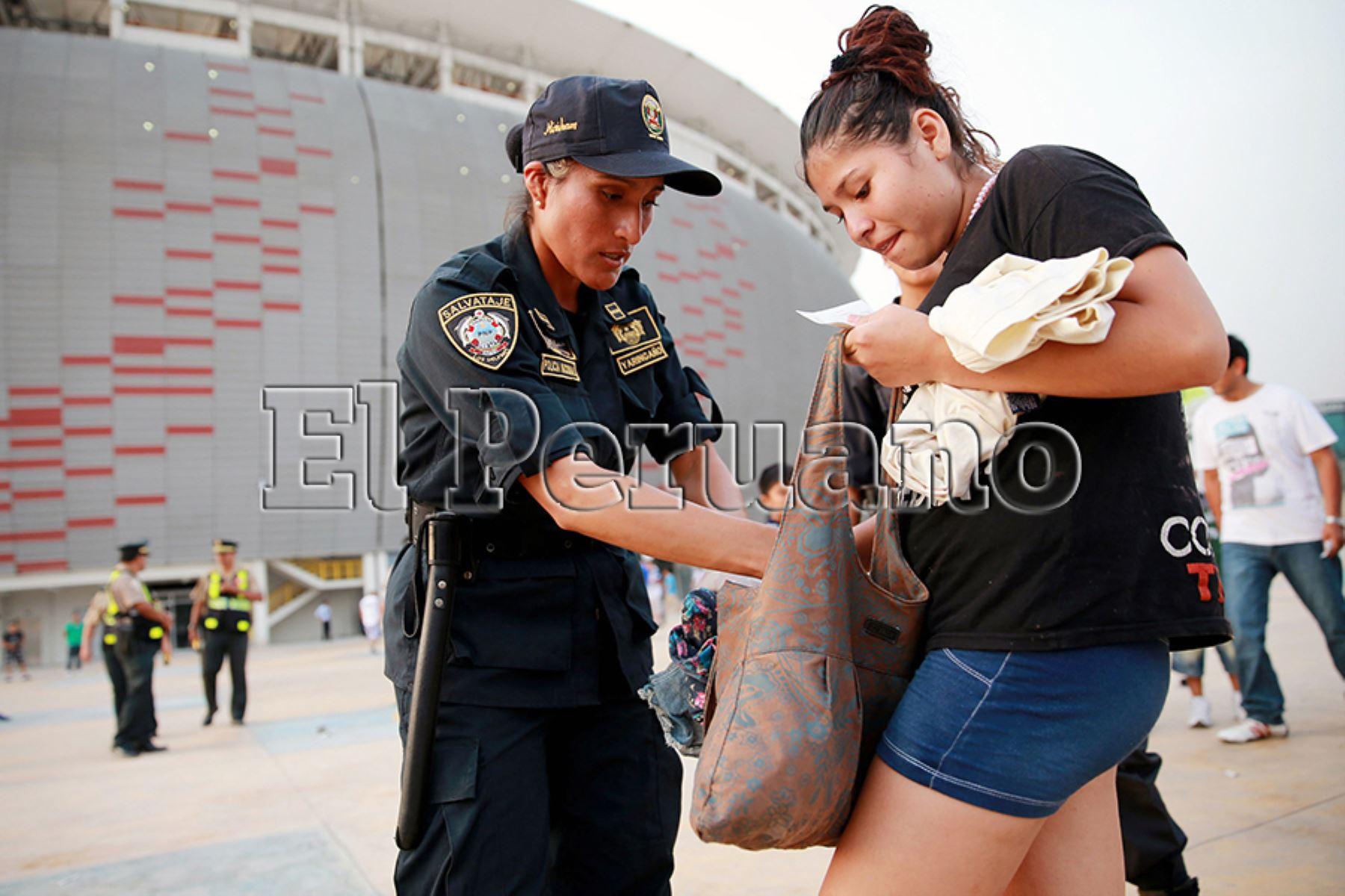 Lima – 15 marzo 2013 / Por medidas de seguridad, miembro de la Policía Femenina, revisa el bolso de una de las asistentes al ingreso del Estadio Nacional.  Foto: Archivo EL PERUANO