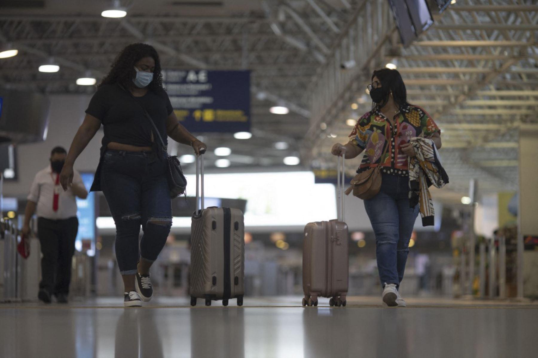 La gente camina en la zona de embarque del aeropuerto internacional Galeao en Río de Janeiro, Brasil, el 13 de abril de 2021, en medio de la pandemia del coronavirus covid-19. Foto: AFP