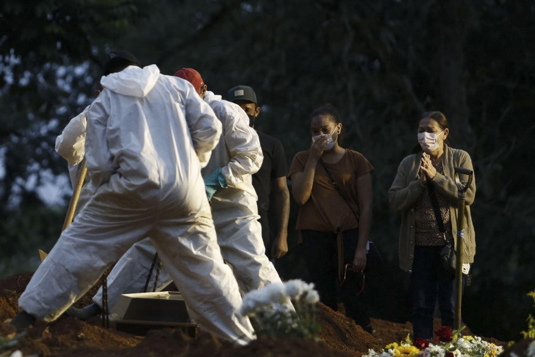La gente llora mientras un familiar es enterrado por trabajadores del cementerio con equipo de protección como medida preventiva contra la propagación de la enfermedad del nuevo coronavirus, covid-19, en el cementerio de Vila Formosa en Sao Paulo, Brasil. Foto: AFP