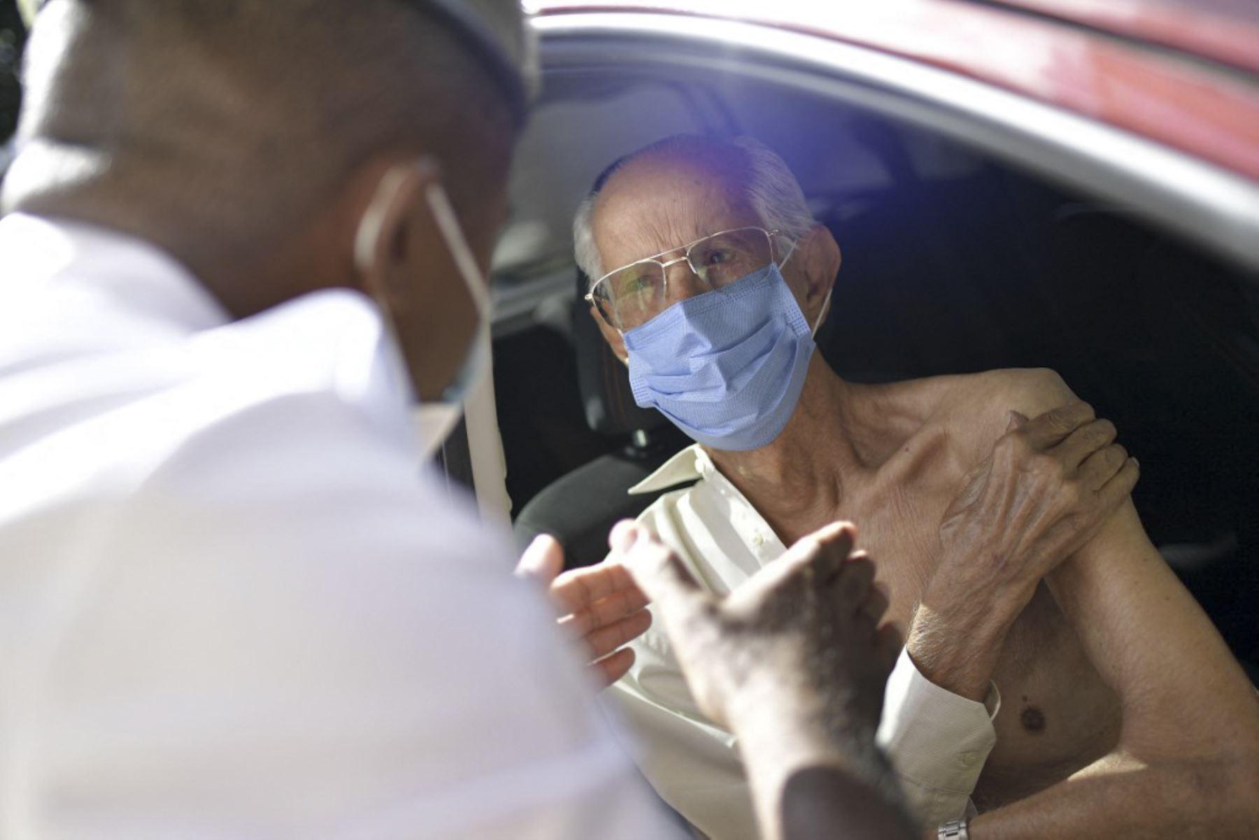 Personal militar del Ejército Brasileño da instrucciones luego de vacunar a un anciano mayor de 89 años, con la segunda dosis de la vacuna AstraZeneca / Oxford contra el nuevo coronavirus, covid-19, en un centro de vacunación drive-through en Belo Horizonte, Estado de Minas Gerais, Brasil. Foto: AFP
