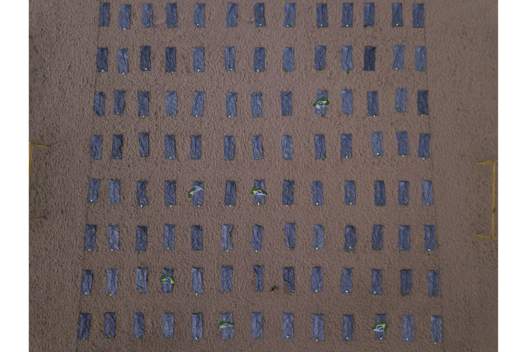 Esta imagen muestra filas de bolsas que simbolizan bolsas para cadáveres en la playa de Copacabana colocadas por activistas de los derechos humanos de Río de Paz durante una protesta contra el manejo del gobierno brasileño de la pandemia de coronavirus, en Río de Janeiro, Brasil. Foto: AFP