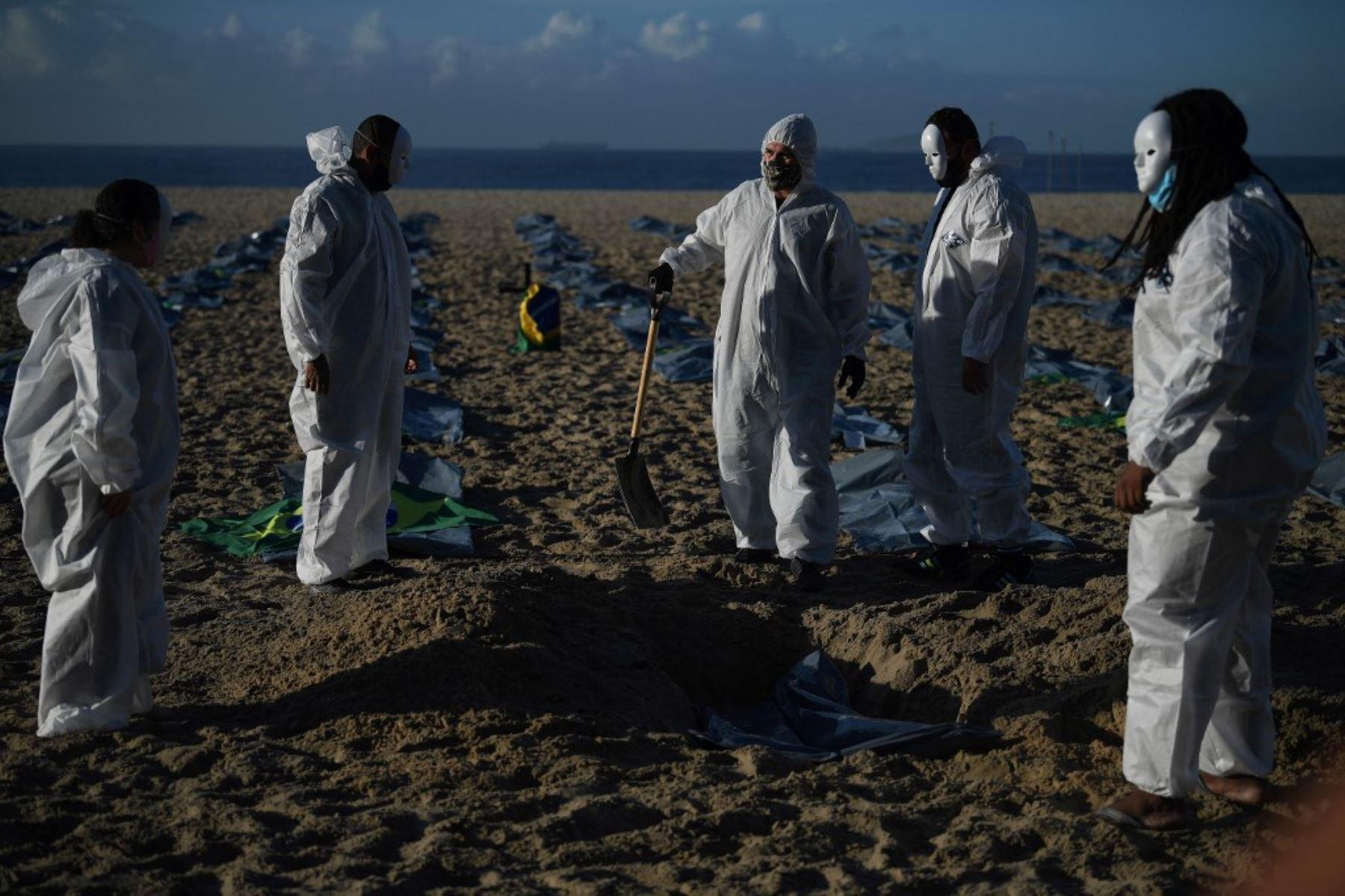 Manifestantes del grupo activista de derechos humanos de Río de Paz cavan una tumba simbólica frente a filas de bolsas que simbolizan bolsas para cadáveres en la playa de Copacabana, durante una protesta contra el manejo del gobierno brasileño de la pandemia de coronavirus, en Río de Janeiro. Foto: AFP