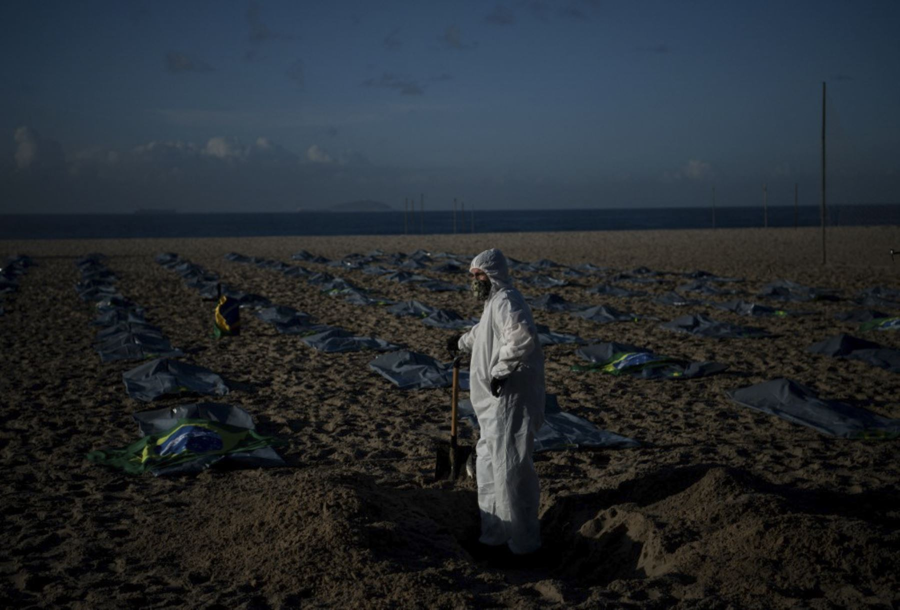 Un manifestante del grupo activista de derechos humanos de Río de Paz cava una tumba simbólica frente a filas de bolsas que simbolizan bolsas para cadáveres en la playa de Copacabana, durante una protesta contra el manejo del gobierno brasileño de la pandemia de coronavirus, en Río de Janeiro. Foto: AFP
