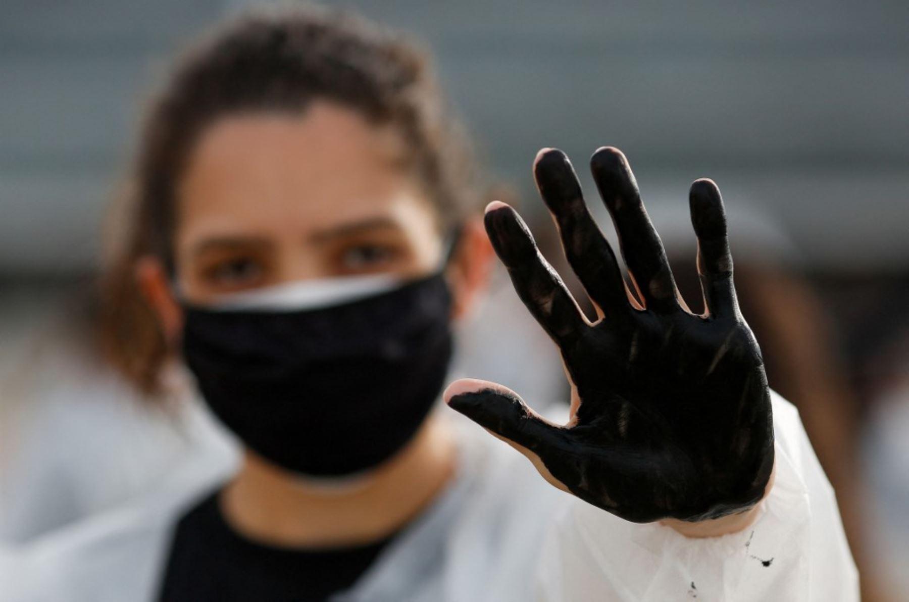 Una enfermera protesta contra el presidente brasileño Jair Bolsonaro y rinden homenaje a los trabajadores de la salud que murieron por complicaciones del nuevo coronavirus covid-19, durante una manifestación frente al Palacio Planalto, en Brasilia. Foto: AFP
