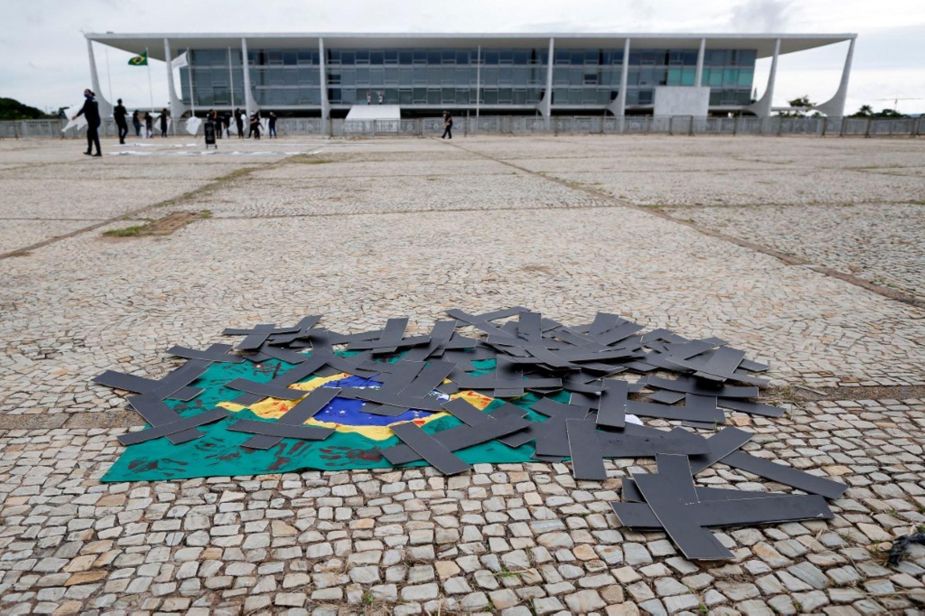 Cruces negras y una bandera brasileña manchada con tinta roja se ven durante una manifestación de enfermeras para protestar contra el presidente brasileño Jair Bolsonaro y rendir homenaje a los trabajadores de la salud que murieron por complicaciones del nuevo coronavirus covid-19, frente al Palacio Planalto en Brasilia. Foto: AFP