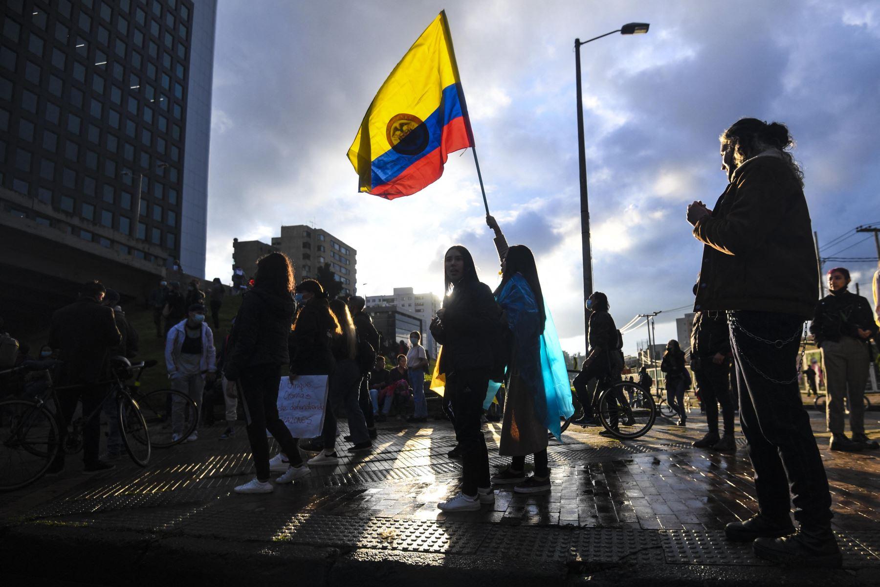 Una mujer ondea una bandera nacional de Colombia durante una protesta contra una reforma fiscal propuesta por el gobierno del presidente colombiano, Iván Duque, en Bogotá. Foto: AFP.