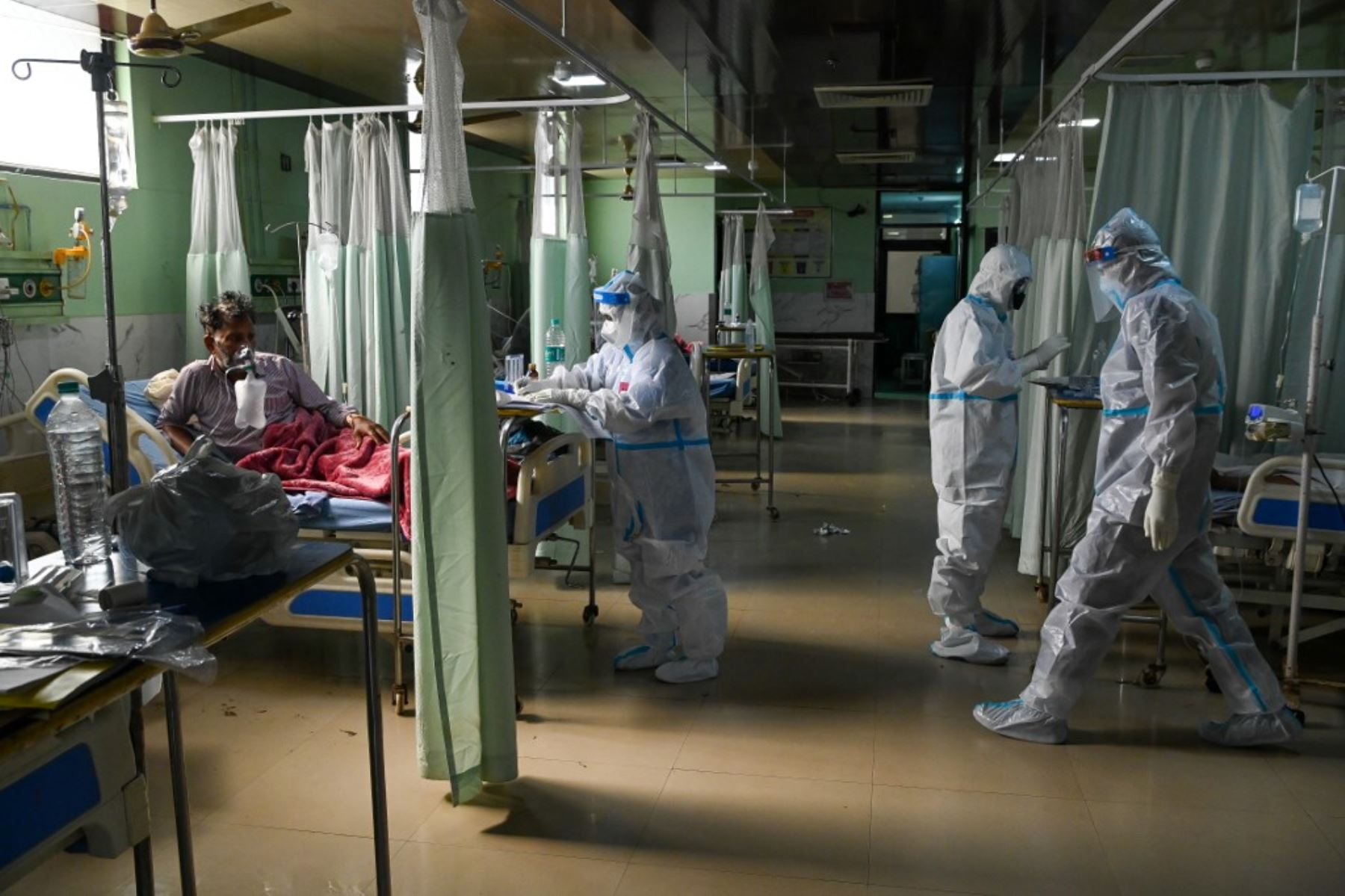 Trabajadores de la salud que usan un equipo de protección personal (equipo de protección personal) atienden al paciente dentro de la Unidad de atención de incentivos (UCI) del hospital de la Universidad Teerthanker Mahaveer (TMU) en Moradabad. Foto: AFP