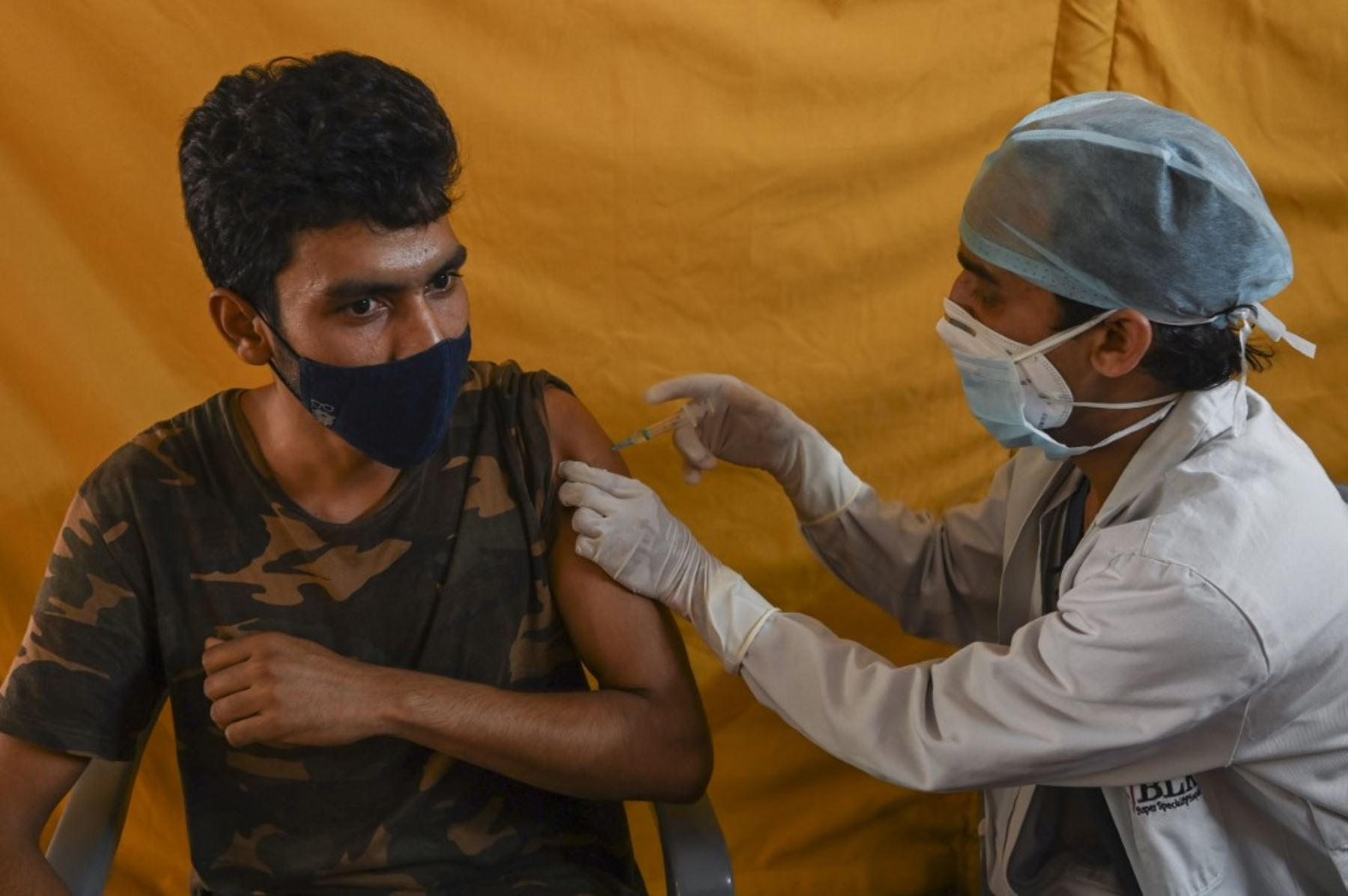 Un trabajador de la salud inocula a un hombre con una dosis de la vacuna Covishield contra el coronavirus covid-19 en un centro de vacunación del hospital BLK-MAX en Nueva Delhi. Foto: AFP