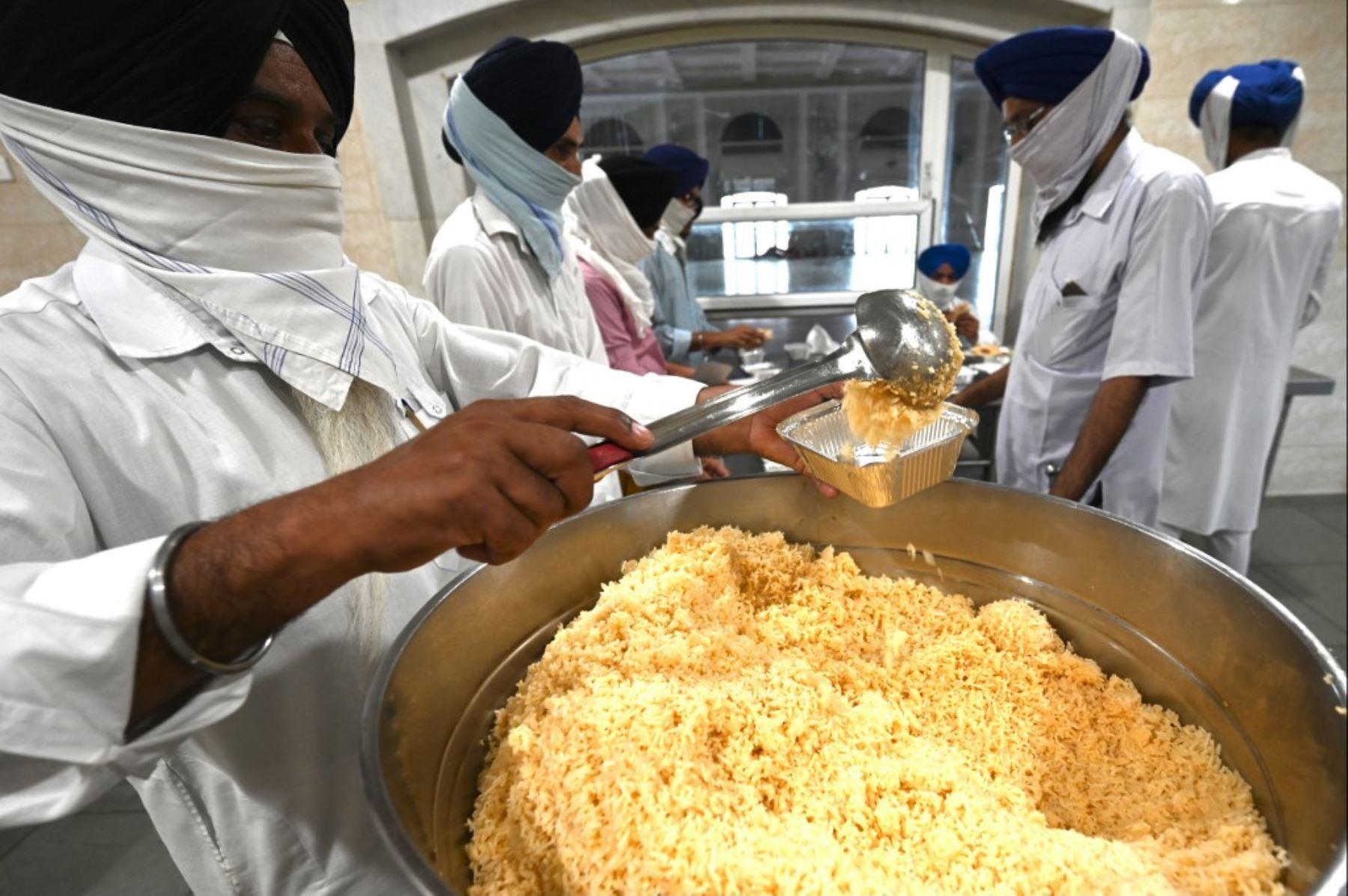 Voluntarios en un Gurudwara (templo sikh) empacan alimentos para pacientes con coronavirus covid-19 aislados en su casa, en la cocina comunitaria de Gurudwara en Nueva Delhi. Foto: AFP