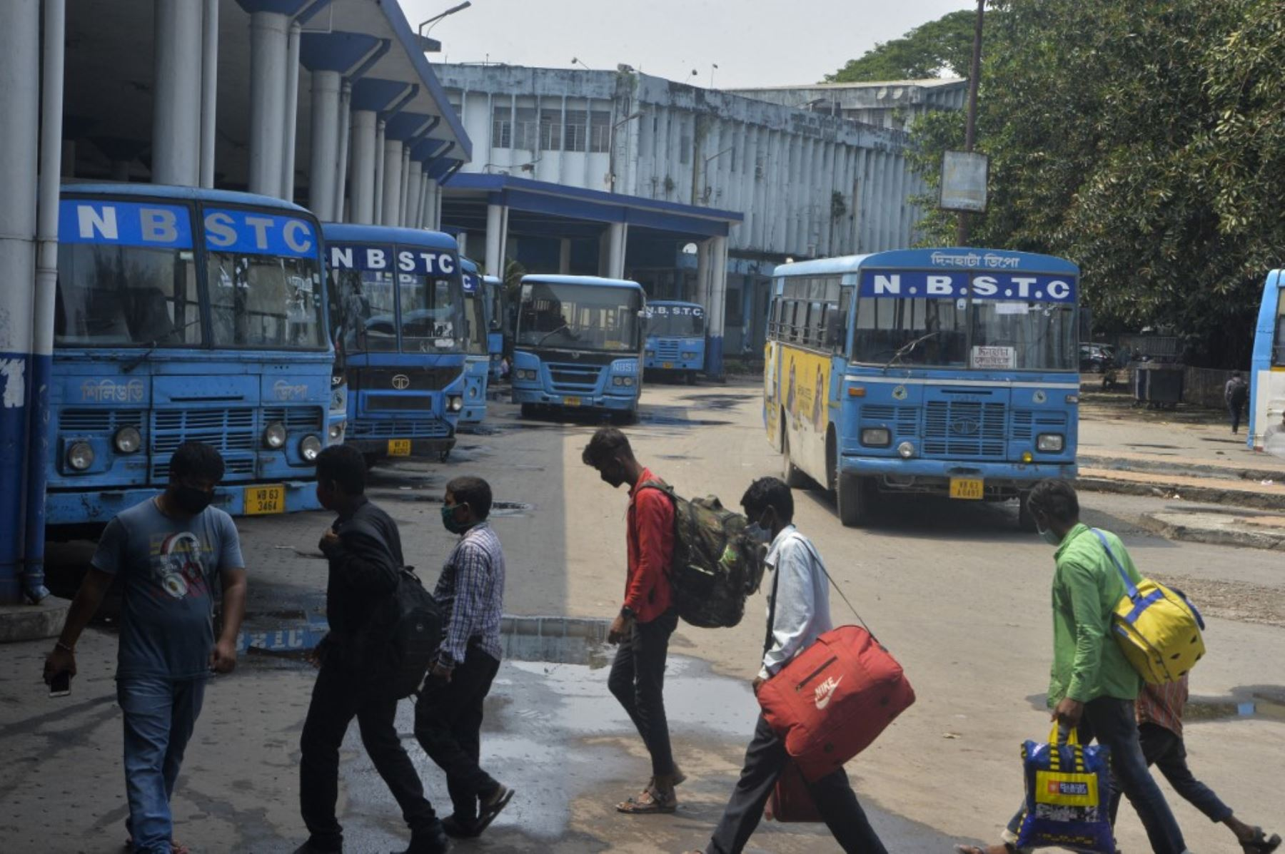 Los pasajeros caminan en la estación de la Corporación de Transporte del Estado de Bengala del Norte en Siliguri el 6 de mayo de 2021 luego del anuncio del departamento de estado de Bengala Occidental de servicios de autobús limitados en medio de la pandemia del coronavirus covid-19. Foto: AFP