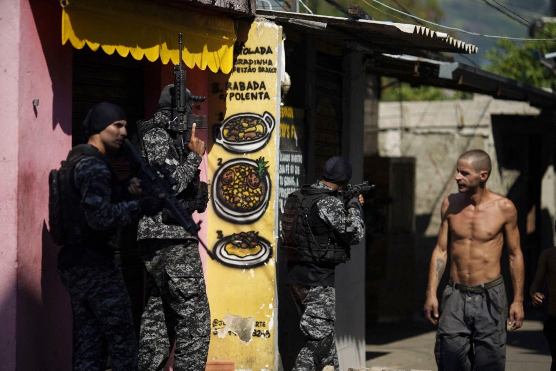 Un residente local observa a los agentes de la Policía Civil de Río que tomaron posición durante un operativo policial contra los narcotraficantes en la favela Jacarezinho en el estado de Río de Janeiro, Brasil, el 6 de mayo de 2021. Foto: AFP