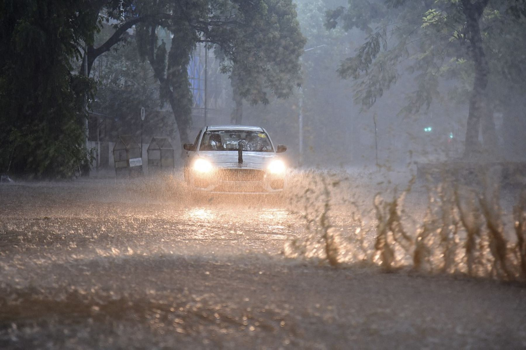 Los viajeros conducen a través de una carretera anegada en medio de las fuertes lluvias en Mumbai el 17 de mayo de 2021, cuando el ciclón Tauktae, con vientos feroces y una amenaza de tormenta destructiva, azotaba India, interrumpiendo la respuesta del país a su devastador brote de Covid-19. Foto: AFP