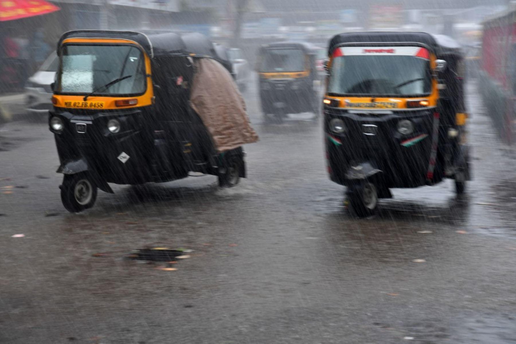 Mototaxis conducen por una calle en medio de las fuertes lluvias del ciclón Tauktae en Mumbai el 17 de mayo de 2021
