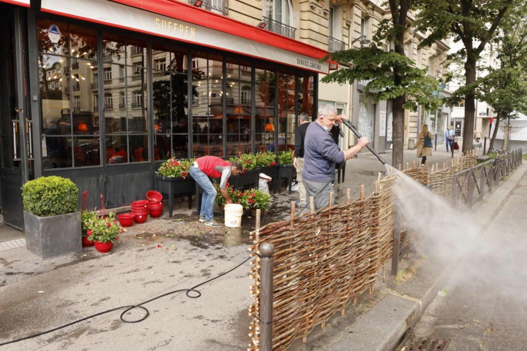 Los empleados están trabajando para instalar la terraza de un café el 17 de mayo de 2021 en París, dos días antes de la reapertura de bares y restaurantes en Francia, el último paso hacia el fin del tercer cierre nacional de Covid-19 en Francia. Foto: AFP