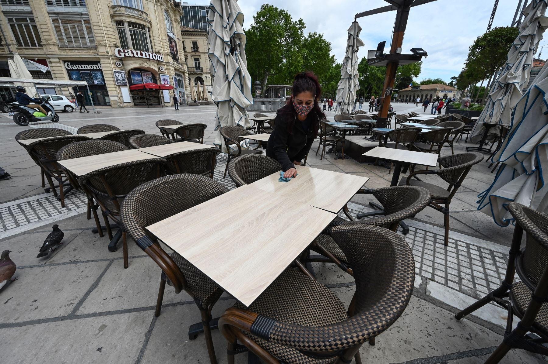 Una mujer instala la terraza de un restaurante en la ciudad de Montpellier, en el sur de Francia, el 17 de mayo de 2021, dos días antes de una reapertura enormemente anticipada de las terrazas de los restaurantes, parte de un alivio del cierre nacional. Foto: AFP