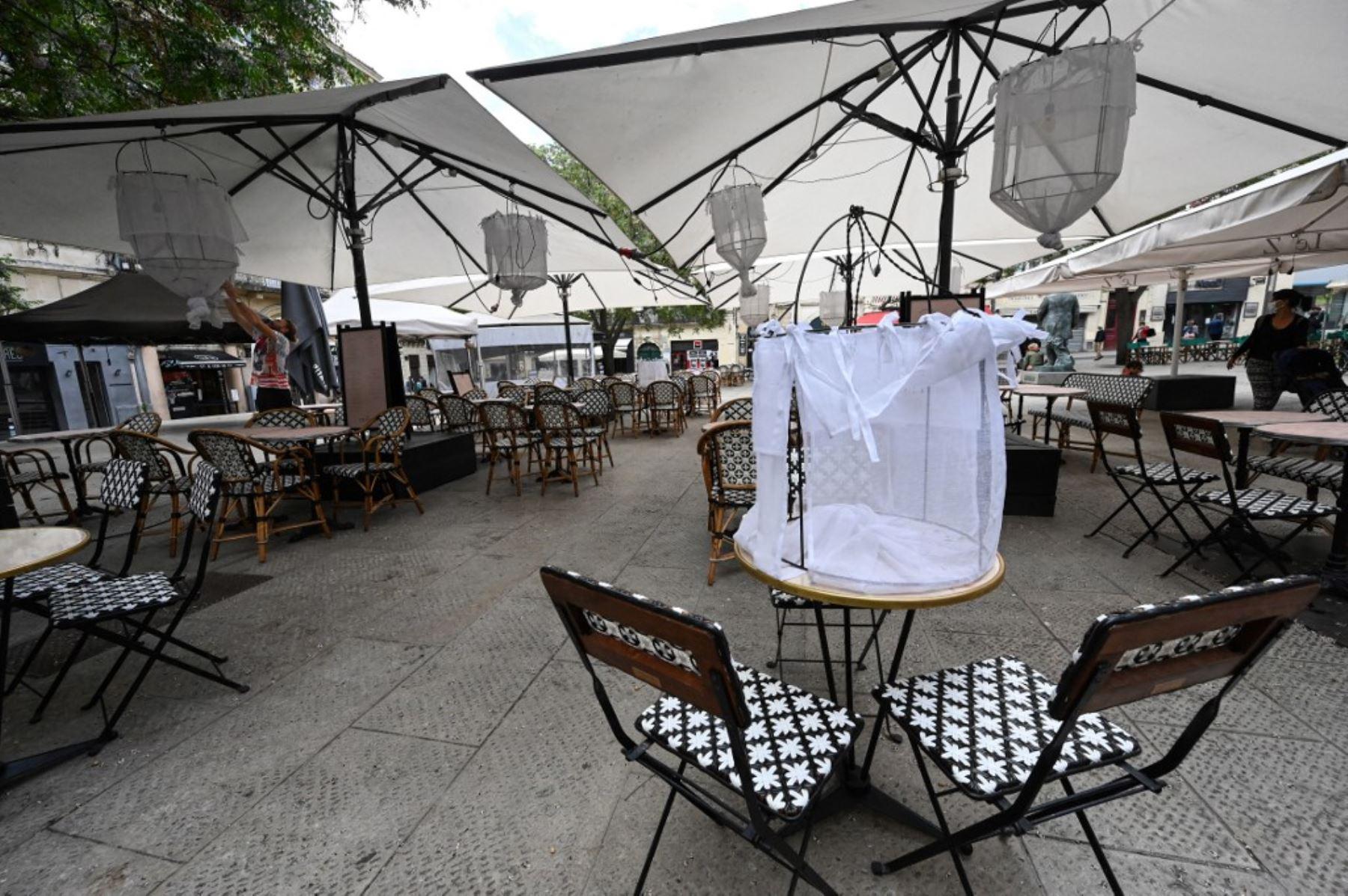 Un hombre instala la terraza de un restaurante en la ciudad de Montpellier, en el sur de Francia, el 17 de mayo de 2021, dos días antes de una reapertura enormemente anticipada de las terrazas de los restaurantes, como parte de un alivio del cierre nacional. Foto: AFP