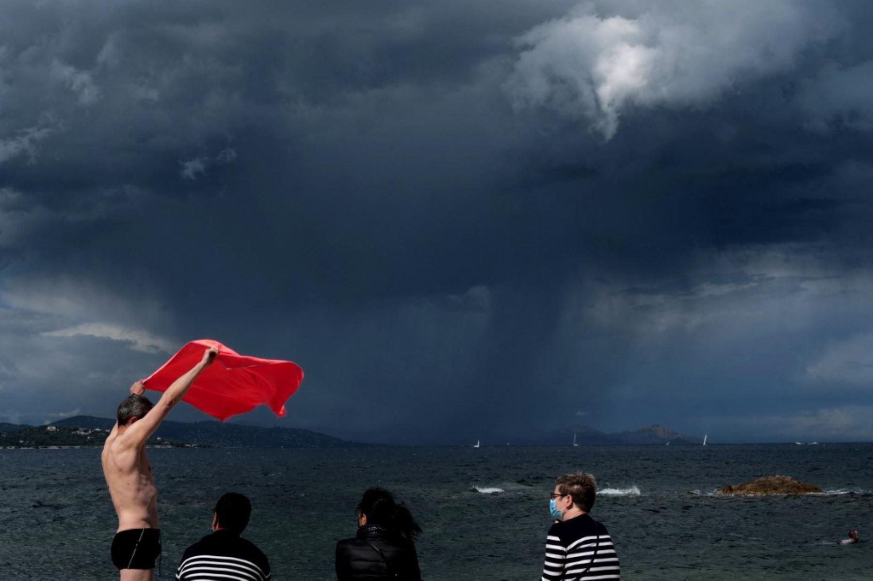 Un hombre retiene su toalla de playa debido al viento cuando se acerca una tormenta, en Saint-Tropez, en el sur de Francia. Foto: AFP