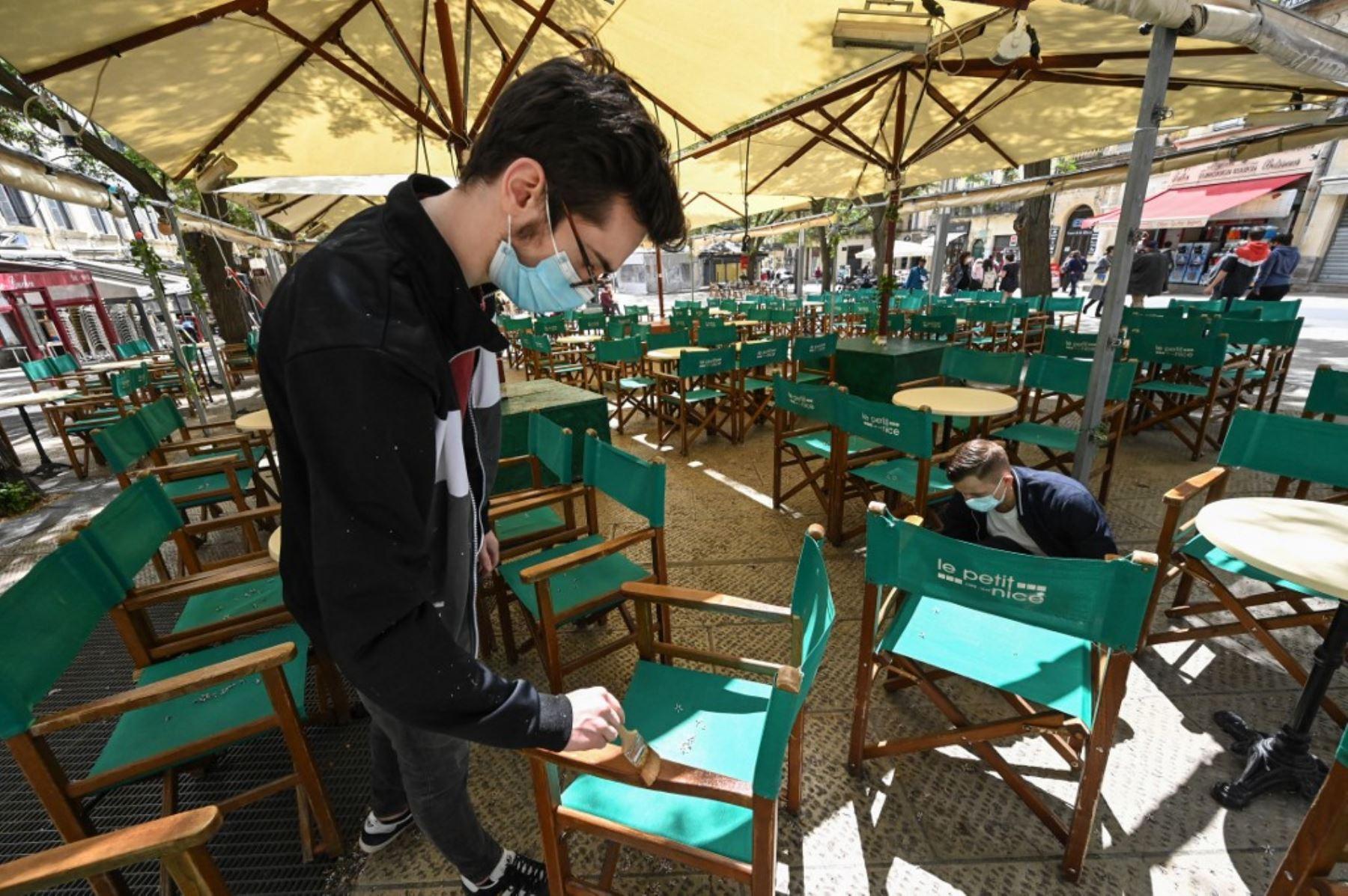 Dos hombres instalan la terraza de un restaurante en la ciudad de Montpellier, en el sur de Francia, el 17 de mayo de 2021, dos días antes de una reapertura enormemente anticipada de las terrazas de los restaurantes, parte de un alivio del cierre nacional. Foto: AFP