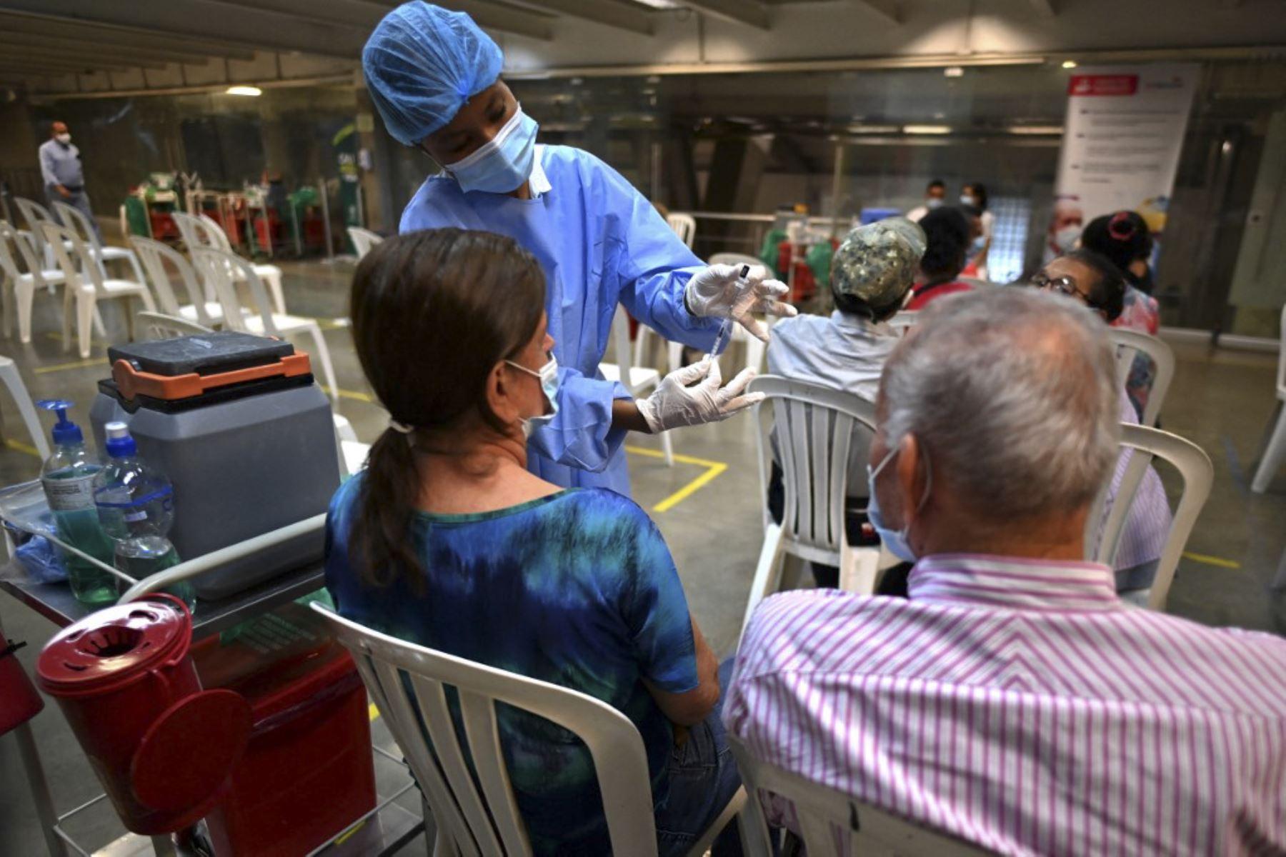 Un trabajador de salud prepara una dosis de la vacuna Pfizer-BioNTech contra covid-19 en el estadio olímpico Pascual Guerrero, en Cali, Colombia. Foto: AFP