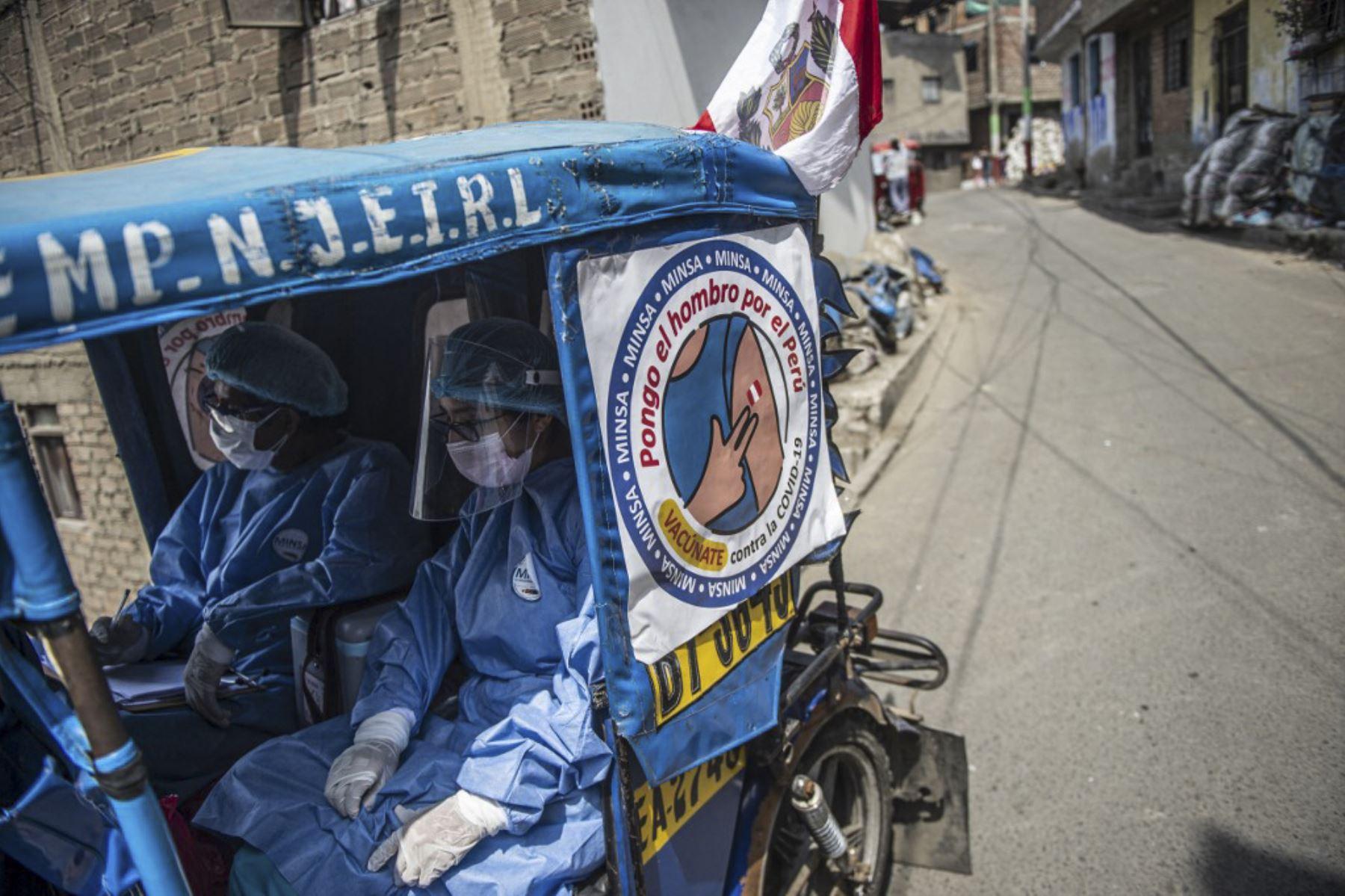 Trabajadores de salud llegan en mototaxi para inocular a ancianos con dosis de la vacuna Pfizer-BioNTech contra covid-19, a su casa del distrito El Agustino en Lima. Foto: AFP