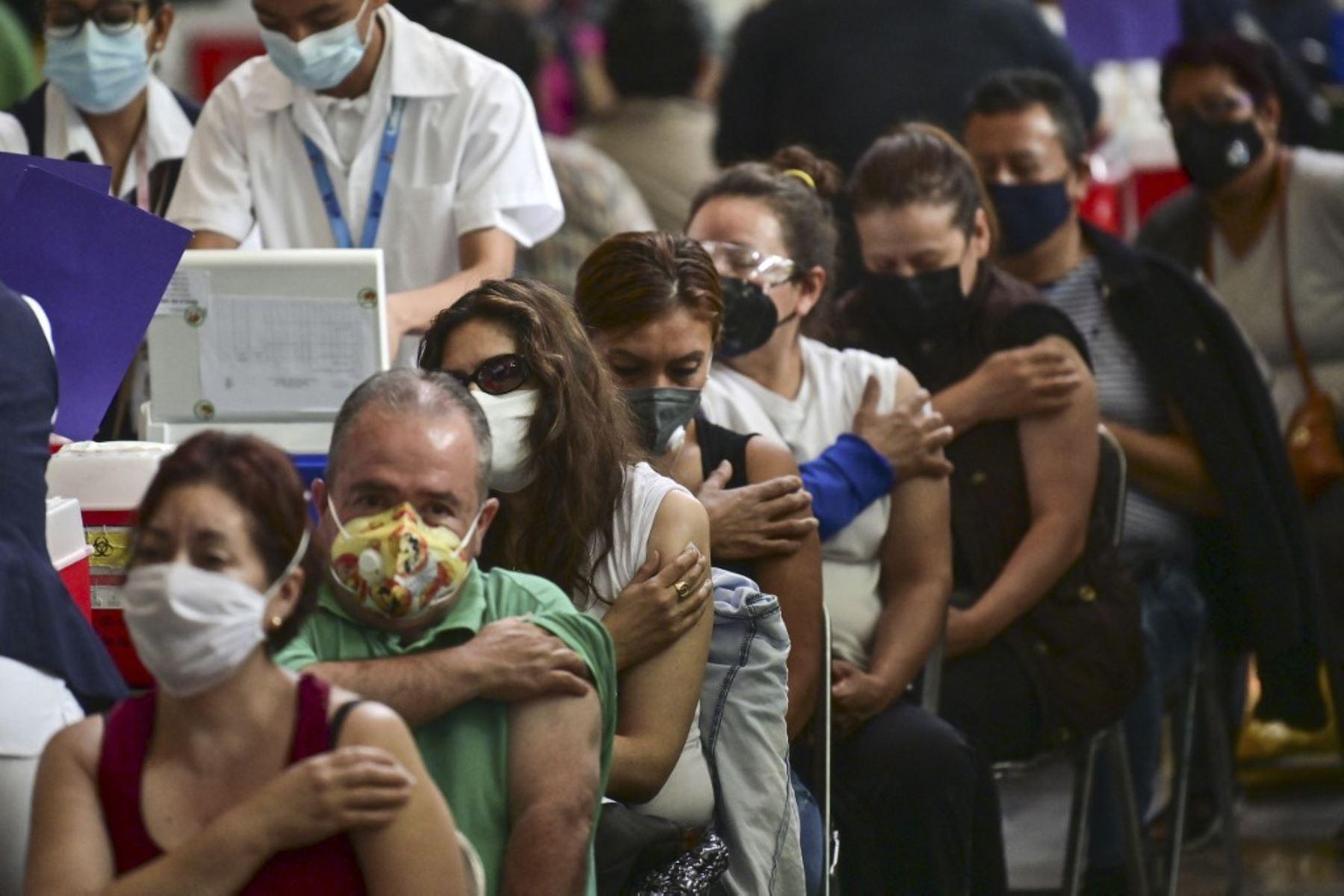 La gente espera luego de recibir dosis de la vacuna Pfizer-BioNTech contra covid-19 en un centro de vacunación para mayores de 50 años instalado en la Biblioteca Vasconcelos, en la Ciudad de México. Foto: AFP