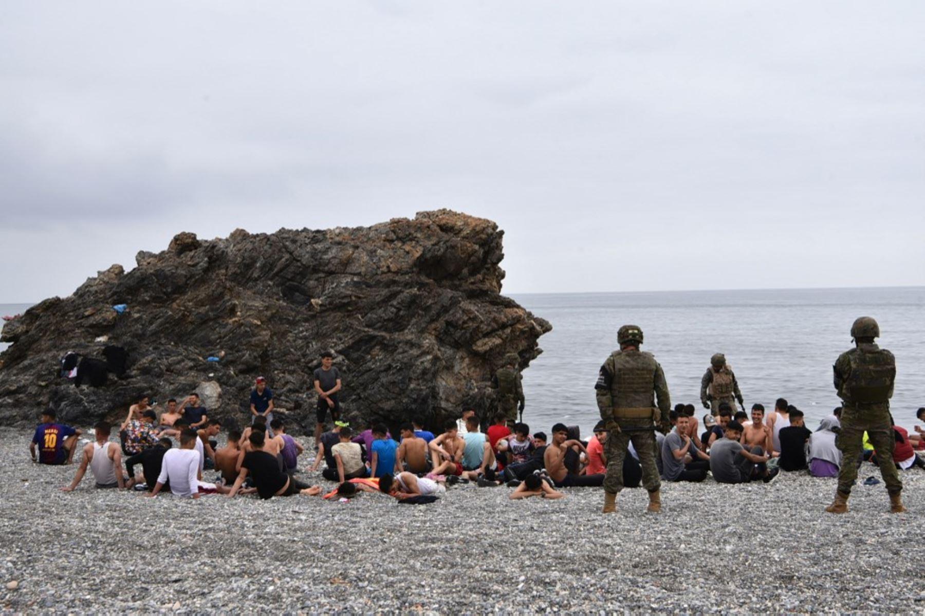 Los migrantes que llegaron nadando al enclave español de Ceuta, descansan mientras los soldados españoles hacen guardia el 18 de mayo de 2021 en Ceuta.  España ha devuelto a Marruecos casi la mitad de los 6.000 migrantes que entraron en su enclave de Ceuta, mientras cientos más intentaban entrar en su otro territorio del norte de África. Foto: AFP