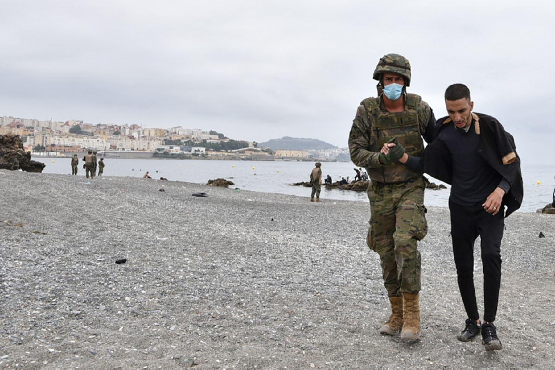 Un soldado español asiste a un migrante que llegó nadando al enclave español de Ceuta, el 18 de mayo de 2021 en Ceuta. - España ha devuelto a Marruecos casi la mitad de los 6.000 migrantes que entraron en su enclave de Ceuta, mientras cientos más intentaban entrar en su otro territorio del norte de África. Foto: AFP