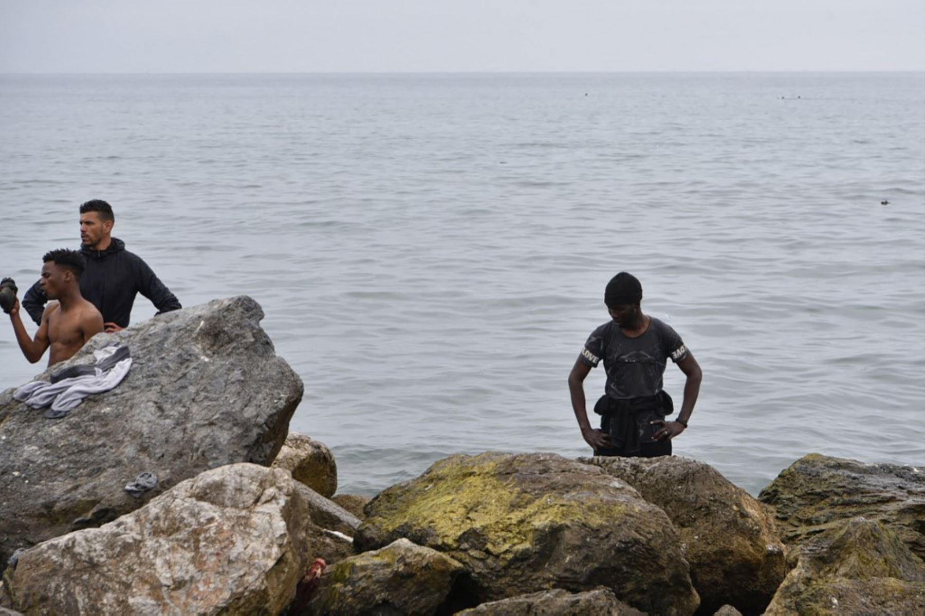Los migrantes descansan tras nadar hasta el enclave español de Ceuta, el 18 de mayo de 2021 en Ceuta. - España ha devuelto a Marruecos casi la mitad de los 6.000 migrantes que entraron en su enclave de Ceuta, mientras cientos más intentaban entrar en su otro territorio del norte de África. Foto: AFP