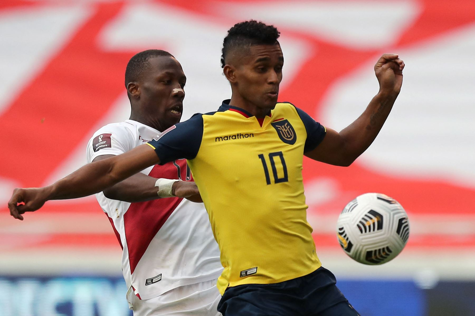 El ecuatoriano Juan Cazares y el peruano Luis Advincula compiten por el balón durante su partido de fútbol de clasificación sudamericano para la Copa Mundial de la FIFA Qatar 2022 en el Estadio Rodrigo Paz Delgado en Quito. Foto: AFP
