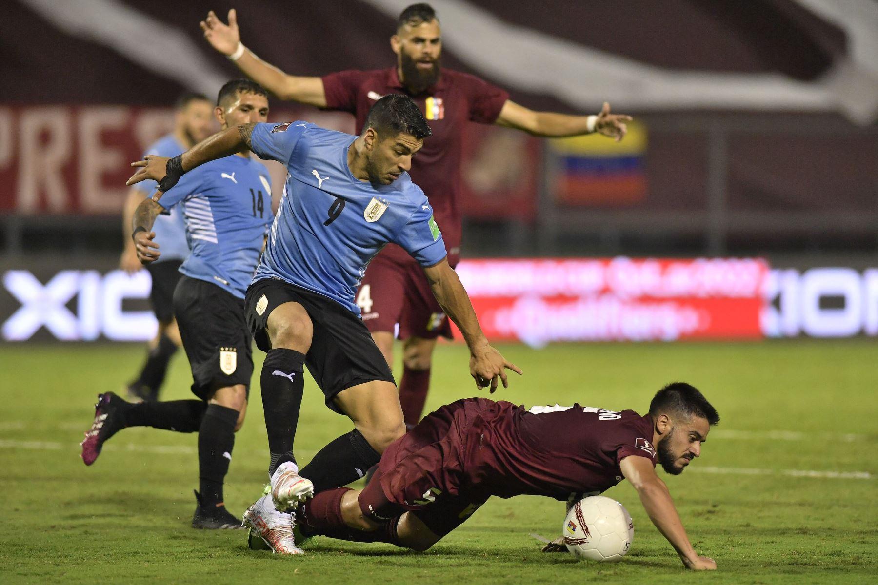 El uruguayo Luis Suárez y el venezolano Junior Moreno compiten por el balón durante su partido de fútbol de clasificación sudamericano para la Copa Mundial de la FIFA Qatar 2022 en el Estadio Olímpico de la UCV en Caracas. Foto: AFP