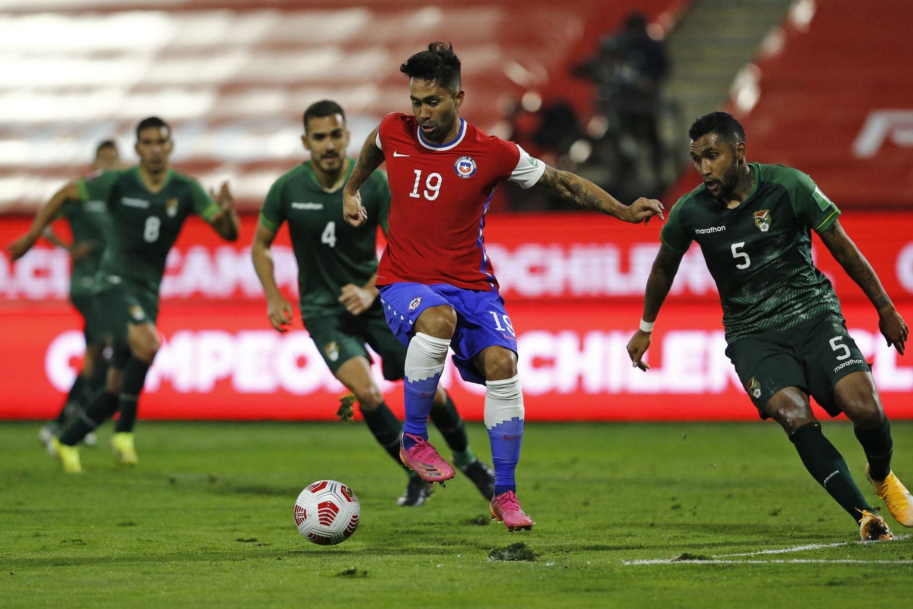 El chileno Luis Jiménez controla el balón junto al boliviano Luis Barboza durante su partido clasificatorio sudamericano para la Copa Mundial de la FIFA Catar 2022 en el Estadio Nacional de Santiago. Foto: AFP