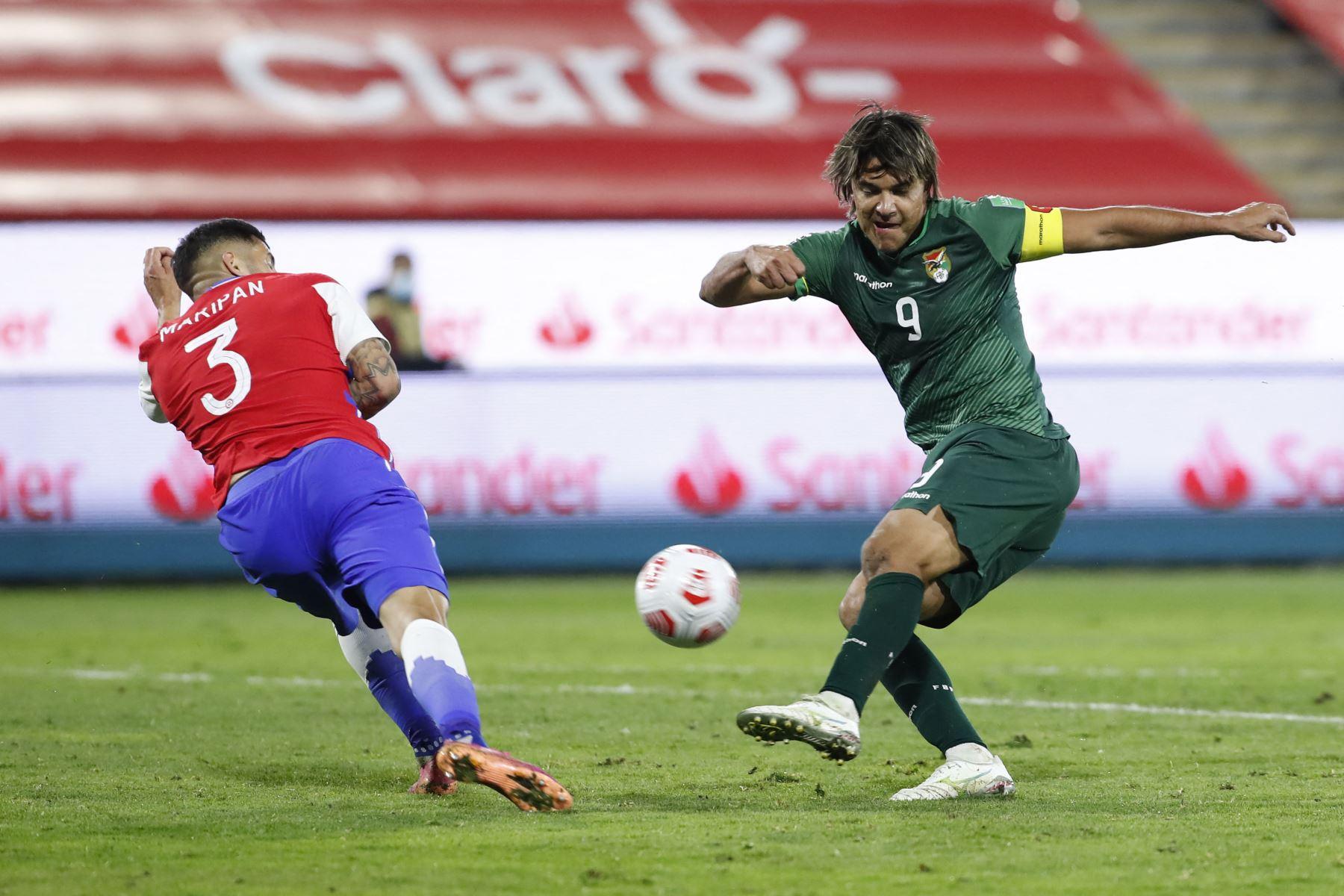 El chileno Guillermo Maripan  y el boliviano Marcelo Martins compiten por el balón durante el partido de clasificación sudamericano para la Copa Mundial de la FIFA Qatar 2022 en el Estadio Nacional de Santiago. Foto: AFP