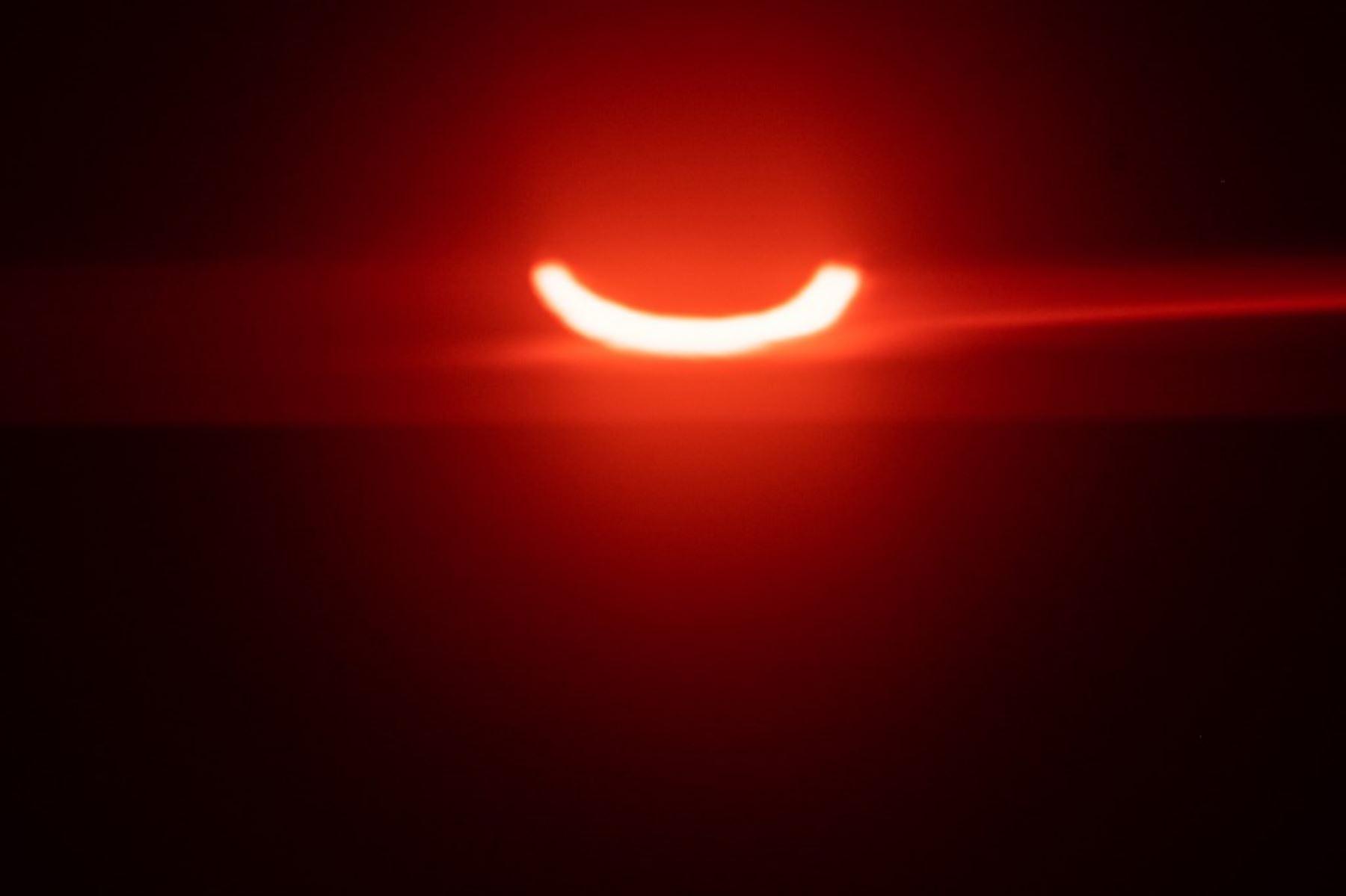 """Un sol eclipsado se eleva sobre Tobermory el 10 de junio de 2021 en Ontario, Canadá. - Los estados canadienses y del noreste de EE. UU. Vieron un raro amanecer eclipsado, mientras que en otras partes del hemisferio norte, este eclipse anular se verá como un anillo exterior delgado y visible del disco solar que no está completamente cubierto por el disco oscuro más pequeño la luna, un llamado """"anillo de fuego"""". Foto: AFP"""