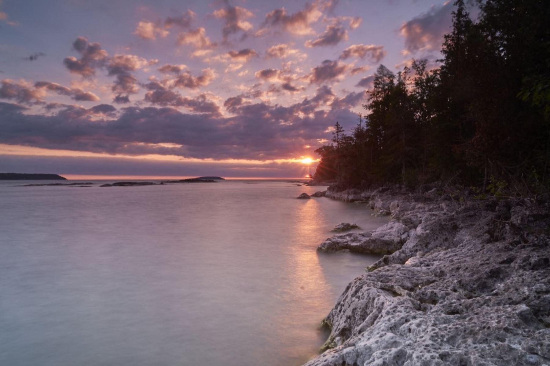 El sol brilla en el agua en el Parque Nacional Marino Fathom Five en Tobermory, Ontario, durante un eclipse solar parcial el 10 de junio de 2021. Foto: AFP