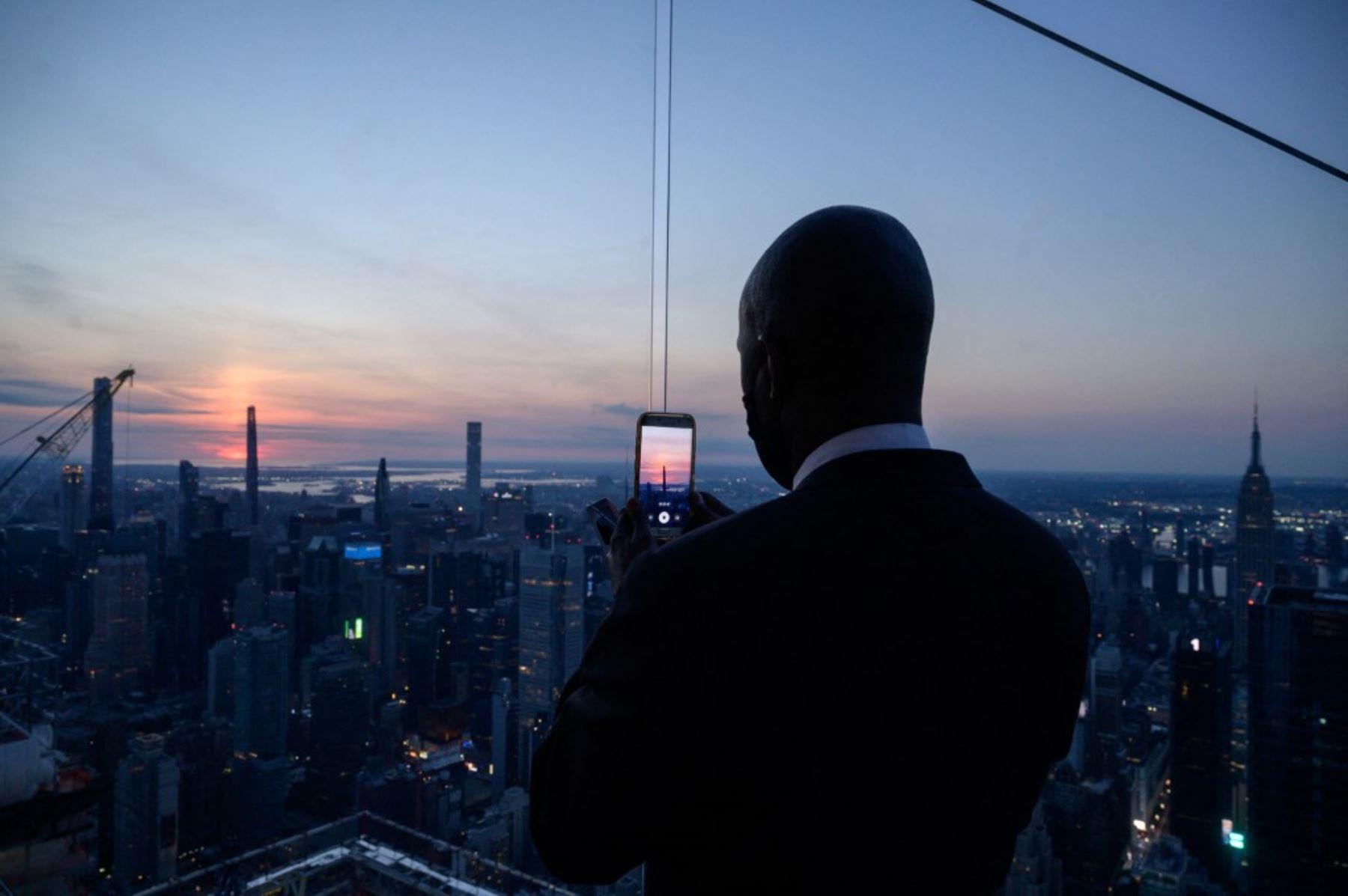 Un hombre que sostiene un teléfono móvil se encuentra frente al horizonte de Manhattan mientras espera el inicio del eclipse solar parcial, en el mirador de Edge, en Nueva York el 10 de junio de 2021. Foto: AFP