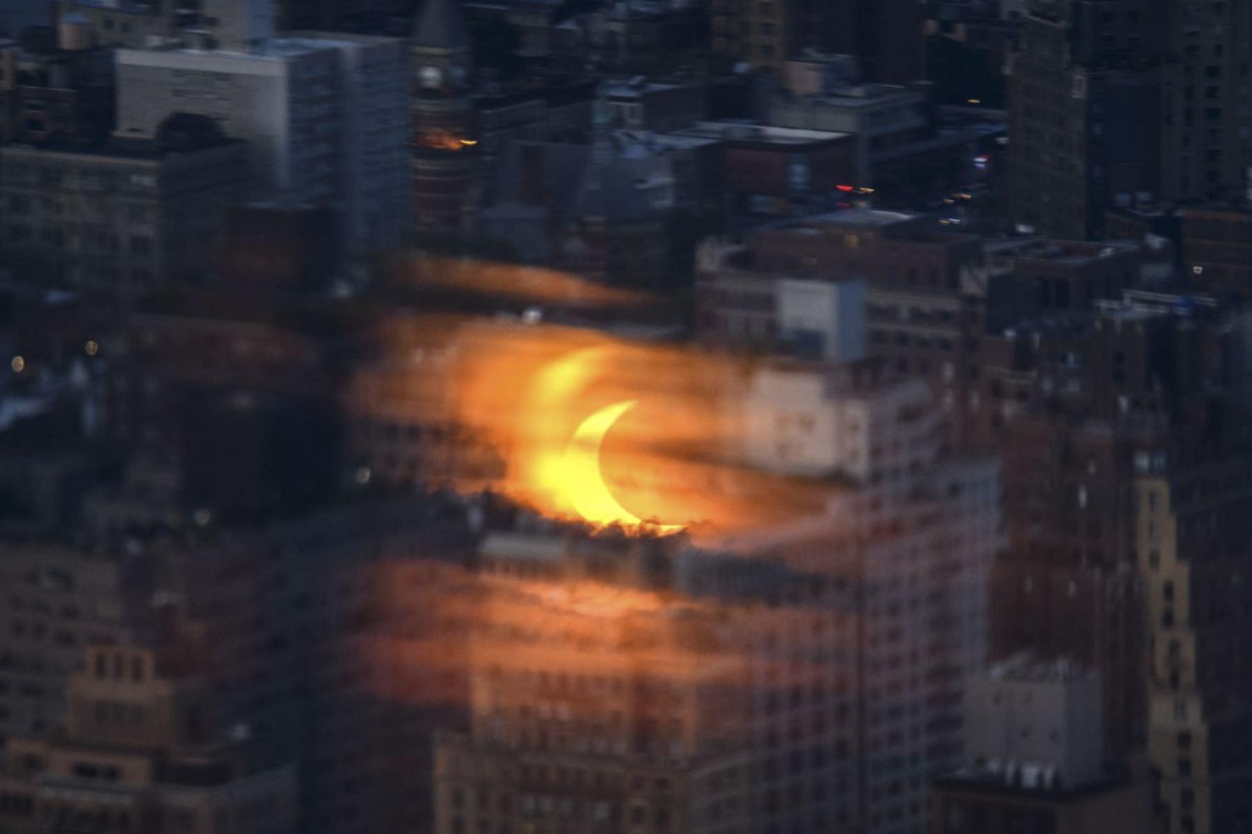 Un eclipse solar parcial se refleja en un panel de vidrio antes de los edificios del horizonte de Manhattan, desde el mirador de Edge en Nueva York el 10 de junio de 2021. Foto: AFP