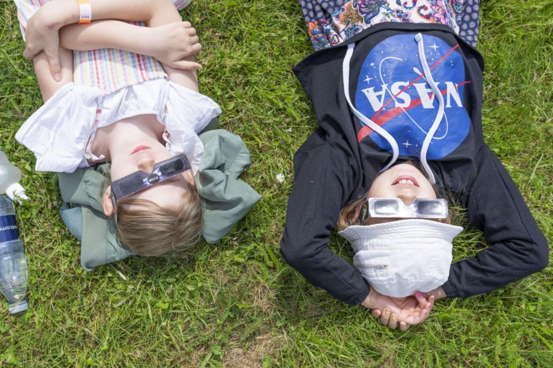 Los niños se acuestan en el césped y miran a través de lentes esperando el eclipse solar parcial en el Observatorio Brorfelde en Tollose, Dinamarca, el 10 de junio de 2021. Foto: AFP