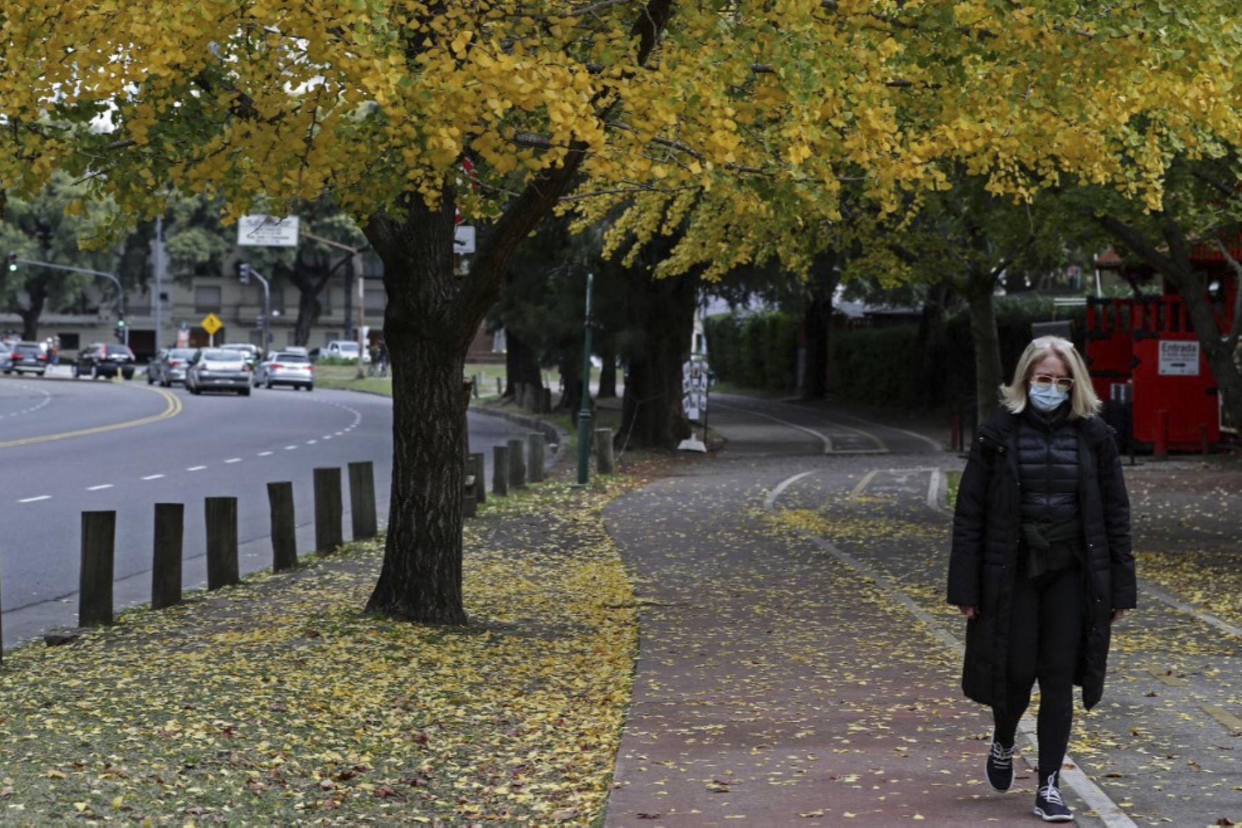 Una mujer con mascarilla protectora camina en un parque en el barrio de Palermo en Buenos Aires. Foto: AFP