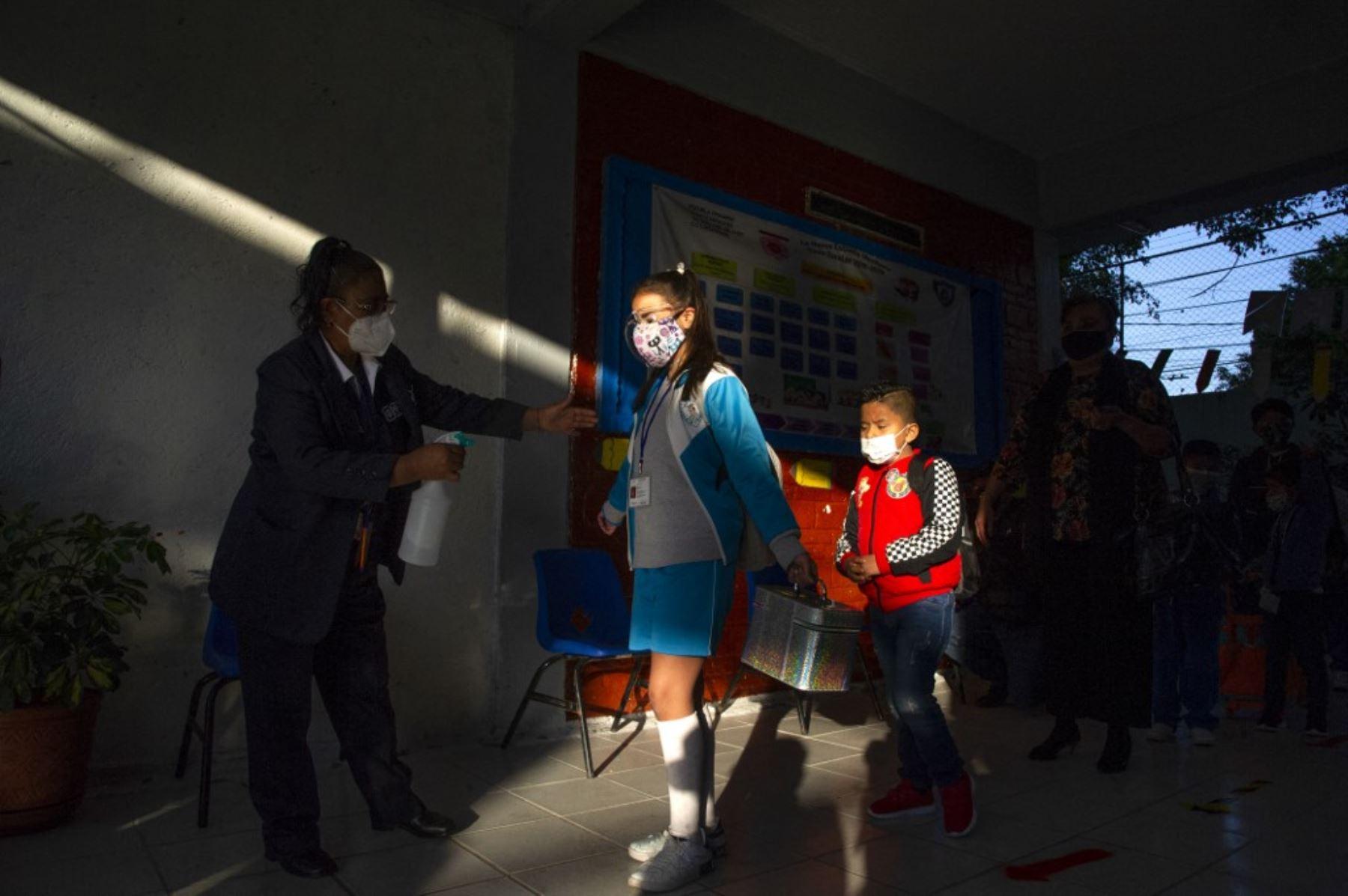 Una niña es desinfectada cuando ingresa a una escuela durante la reanudación de las clases presenciales en la Ciudad de México, luego de que las actividades educativas fueran suspendidas debido a la pandemia del coronavirus covid-19 durante más de un año. Foto: AFP